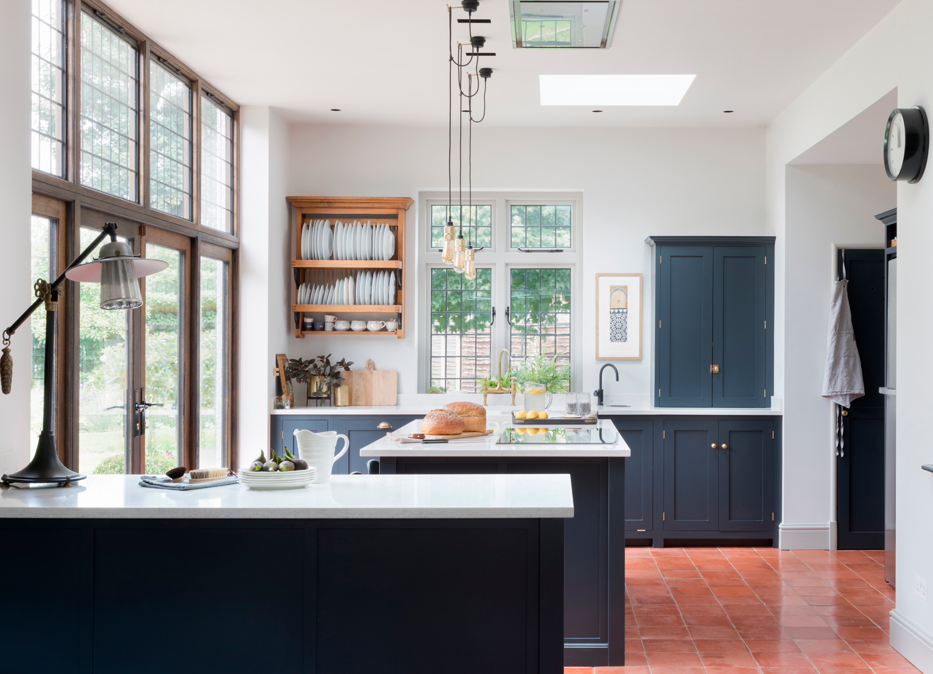 SOLUTION - Dark blue Shaker style kitchen, with antiqued brass taps and hardware.Reclaimed quarry tiles sourced to match the original hall tiles.Full lighting and electrical plan to zone the different areas and create functional, multipurpose lighting.Old window converted into a herb cupboard adds a quirky touch.