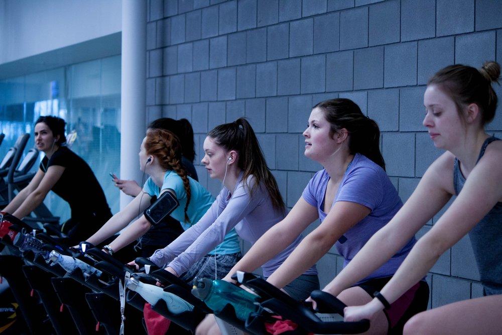 women exercising on bike machines