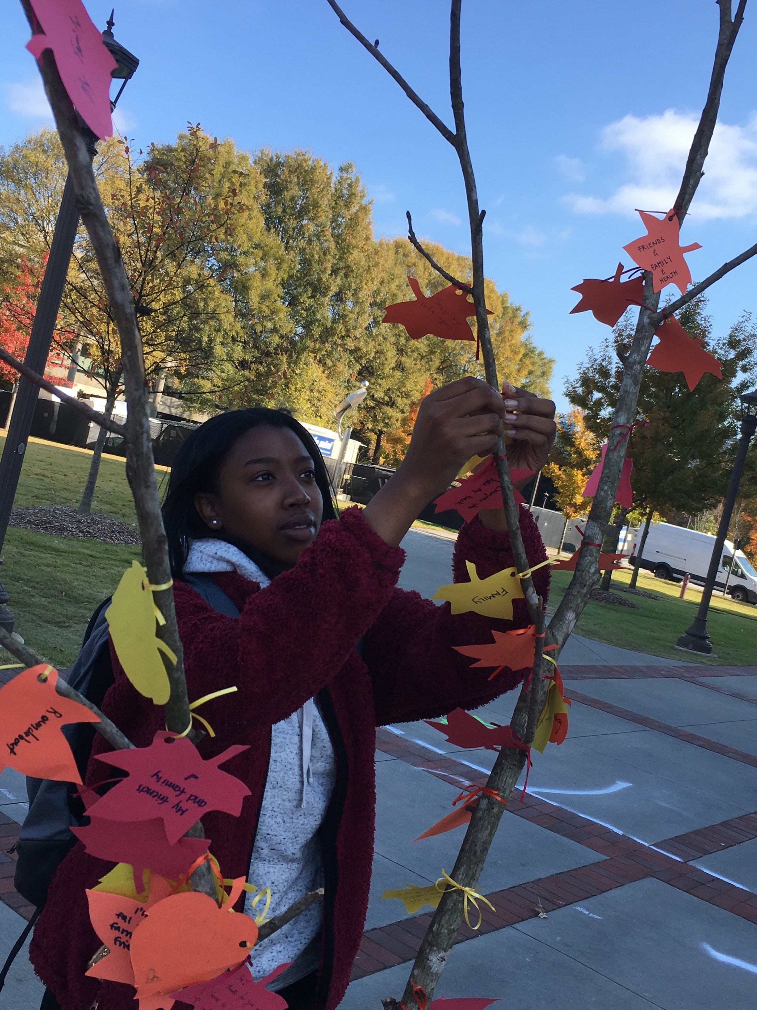 A girl hanging a leaf on the tree.
