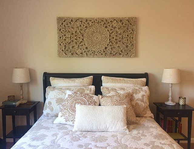 Today's decorating project—hanging this carved wooden wall piece. Unfortunately, my poor hubby had to drill into concrete once again for it, but this time we were prepared with the right drill bit and screws! So pleased with how this piece fills the space over our bed and coordinates with the bedding and lamps! #interiordesign #bedroomdecor #walldecor #pier1love