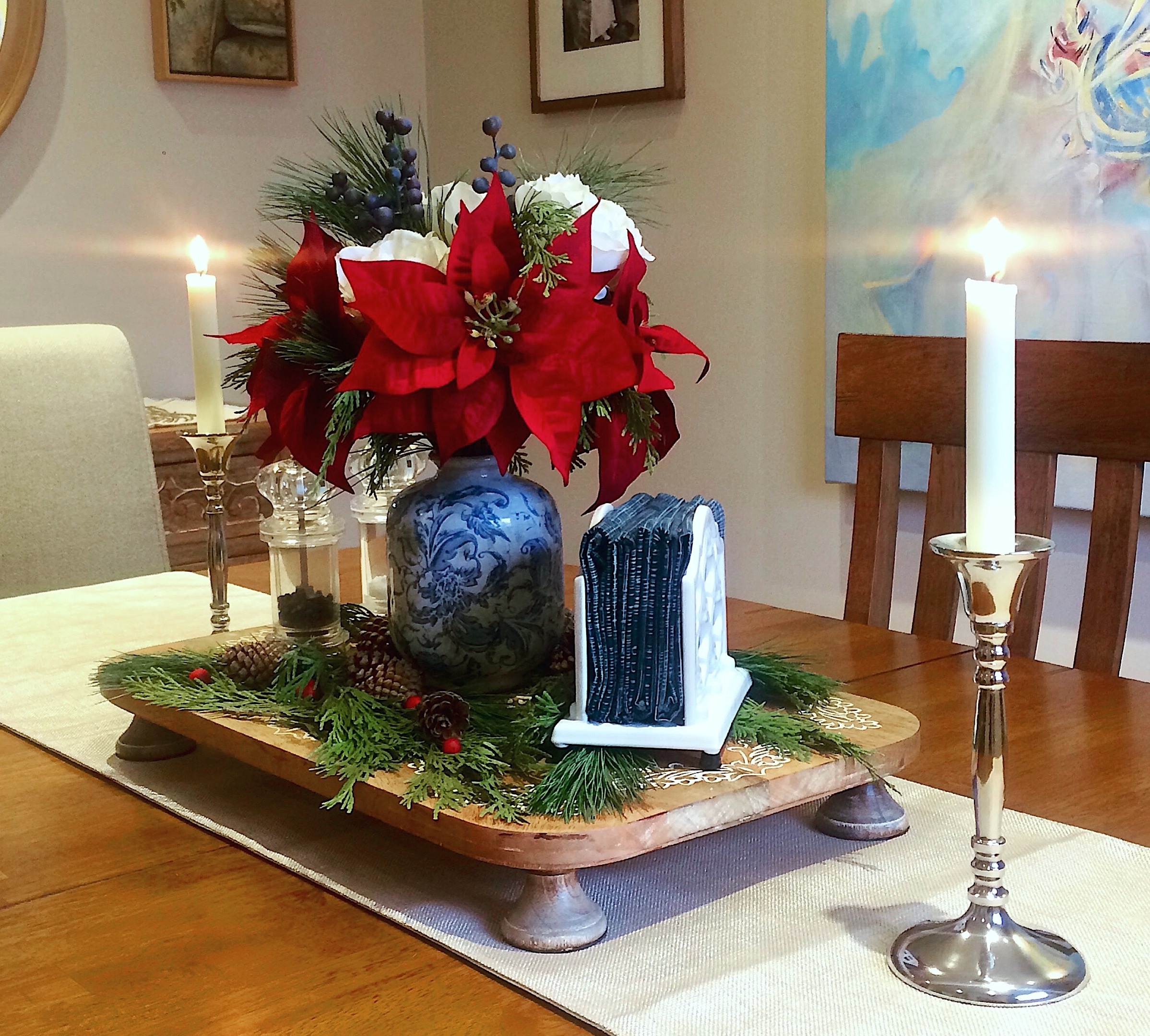 Winter Tablescape.  An arrangement of faux poinsettias and white roses along with scattered evergreen branches, pine cones, and red berries transforms this vignette into a festive holiday centerpiece.