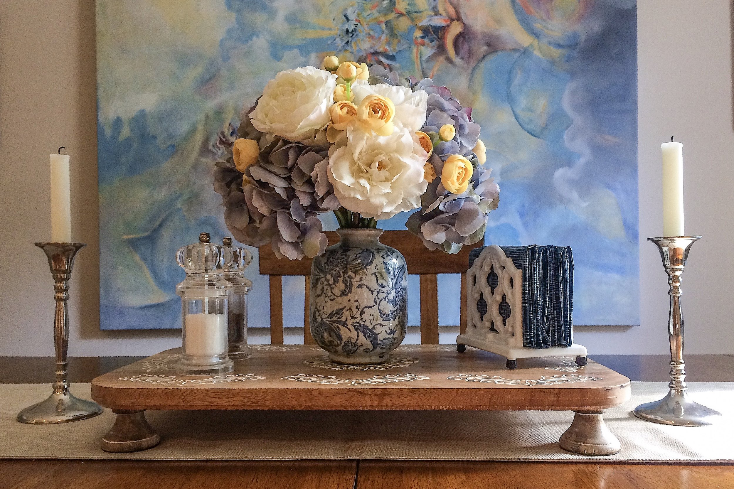 Spring Tablescape.  The faux floral arrangement of pale blue hydrangeas, white roses, and yellow ranunculus captures the pastel hues of spring and ties into the colors of the artwork in the background.