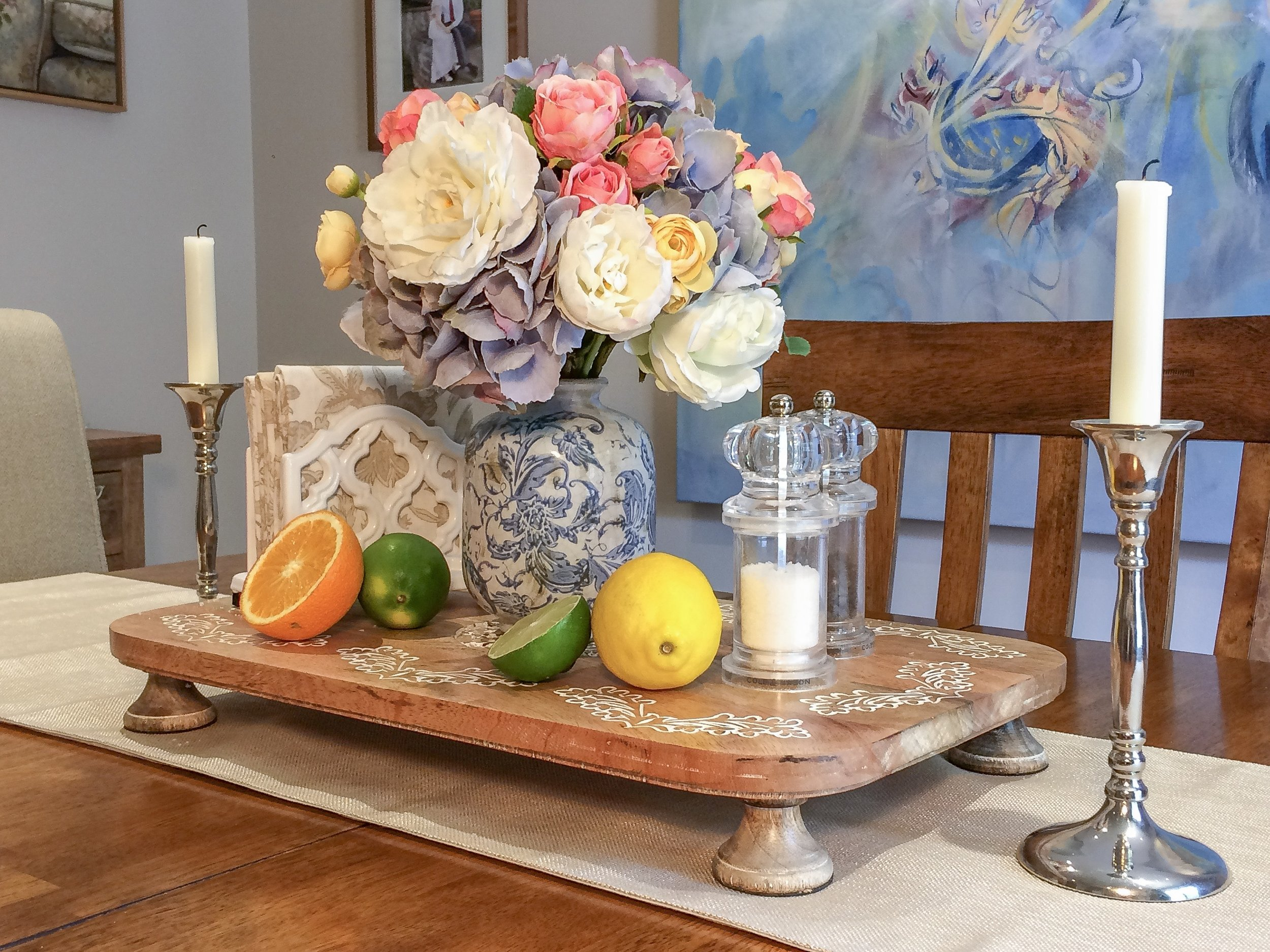 Summer Tablescape . The salmon pink mini roses brighten up the floral arrangement while the citrus fruits add more pops of color and give the centerpiece a more summery vibe. The ivory patterned napkins also help to lighten the display.
