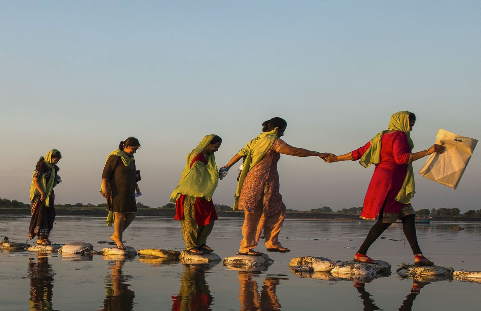 Women cross a wet swath of land by stepping on sand bags