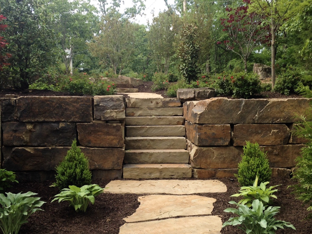 Retaining Wall Installation - From large stone dry stacked boulder walls to masonry retaining walls, we can install one wall or terrace with multiple walls to give you the look and functionality your property deserves.