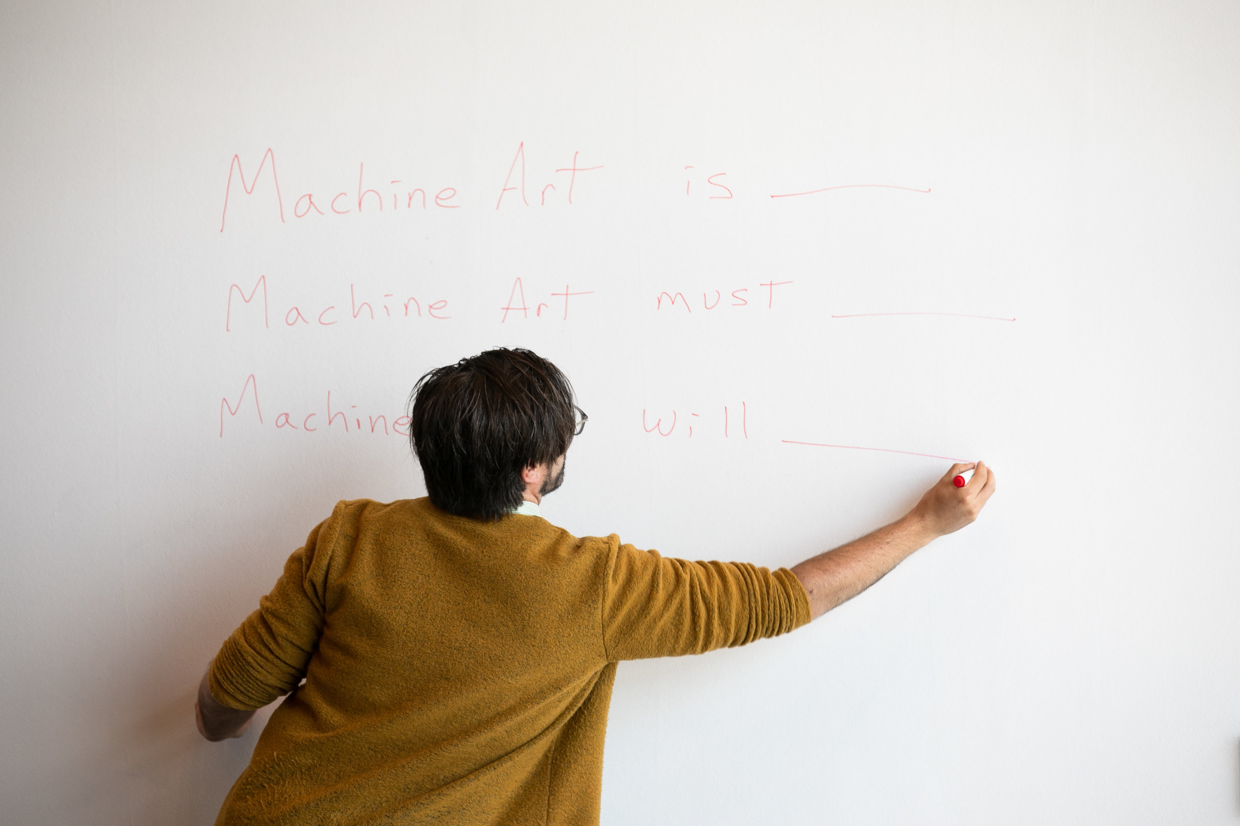"""Eryk Salvaggio presenting prompts for the """"Machinafesto,"""" a human-computer collaboration with the attendees of the """"Machine, Myself & I"""" symposium at swissnex San Francisco on July 12, 2019. PHOTO MYLEEN HOLLERO / SWISSNEX SF."""