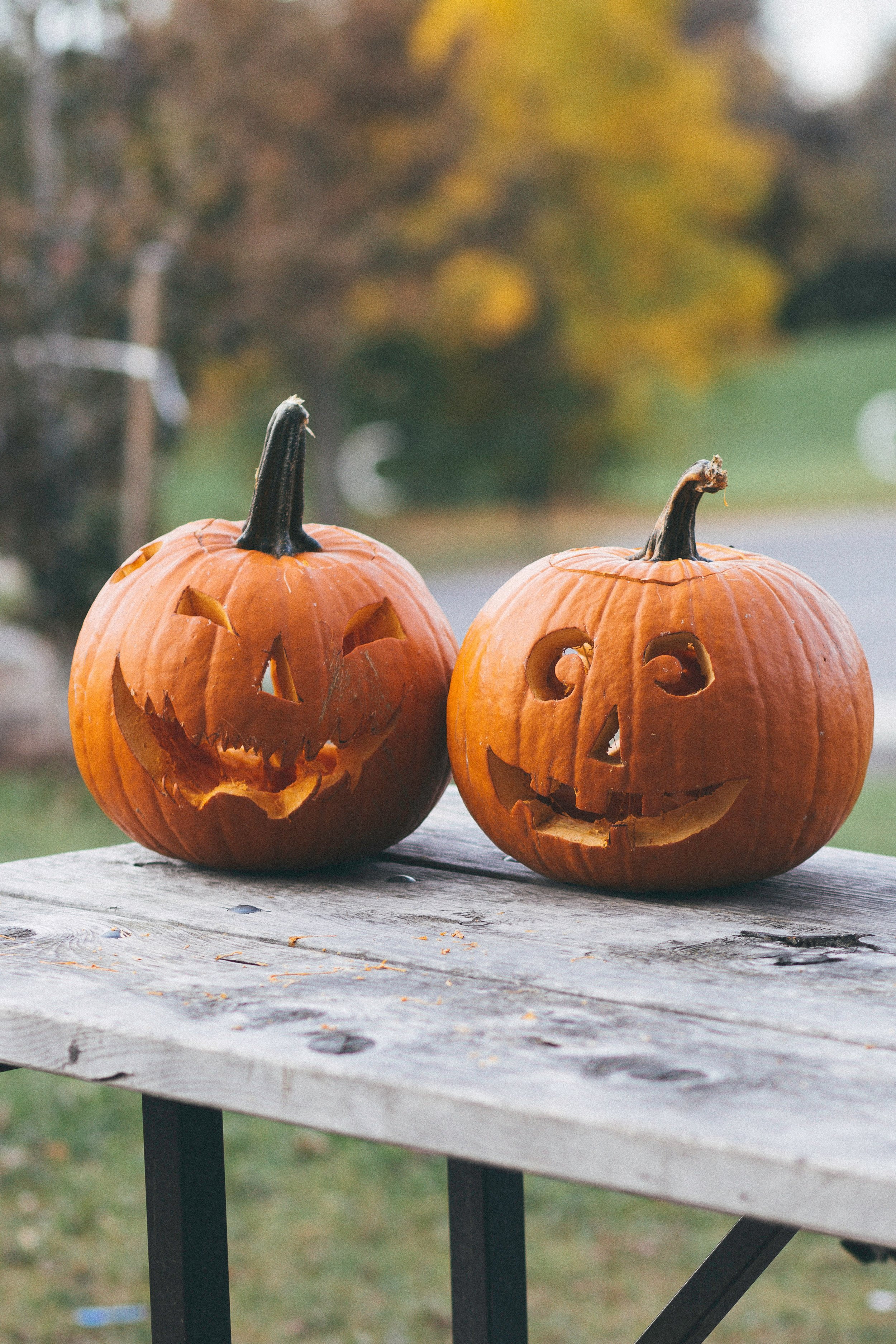 Two carved pumpkins on an outdoor wooden table.