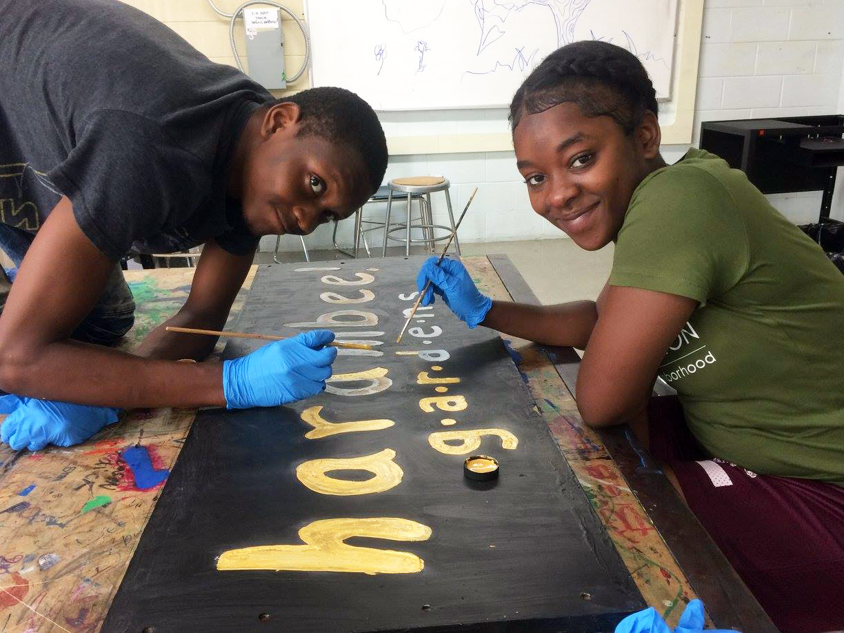 Participants paint new signs for the Harambee Garden.