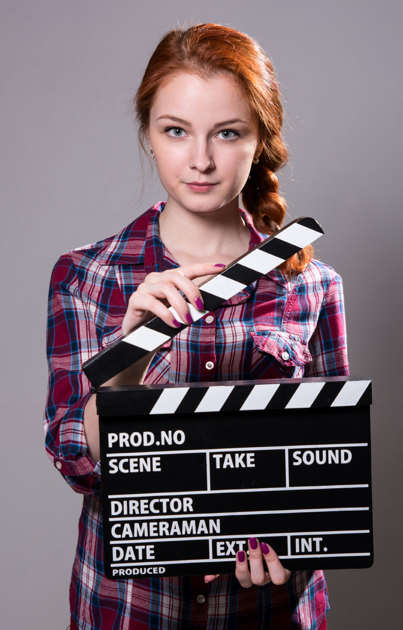 Girl holding clapboard.