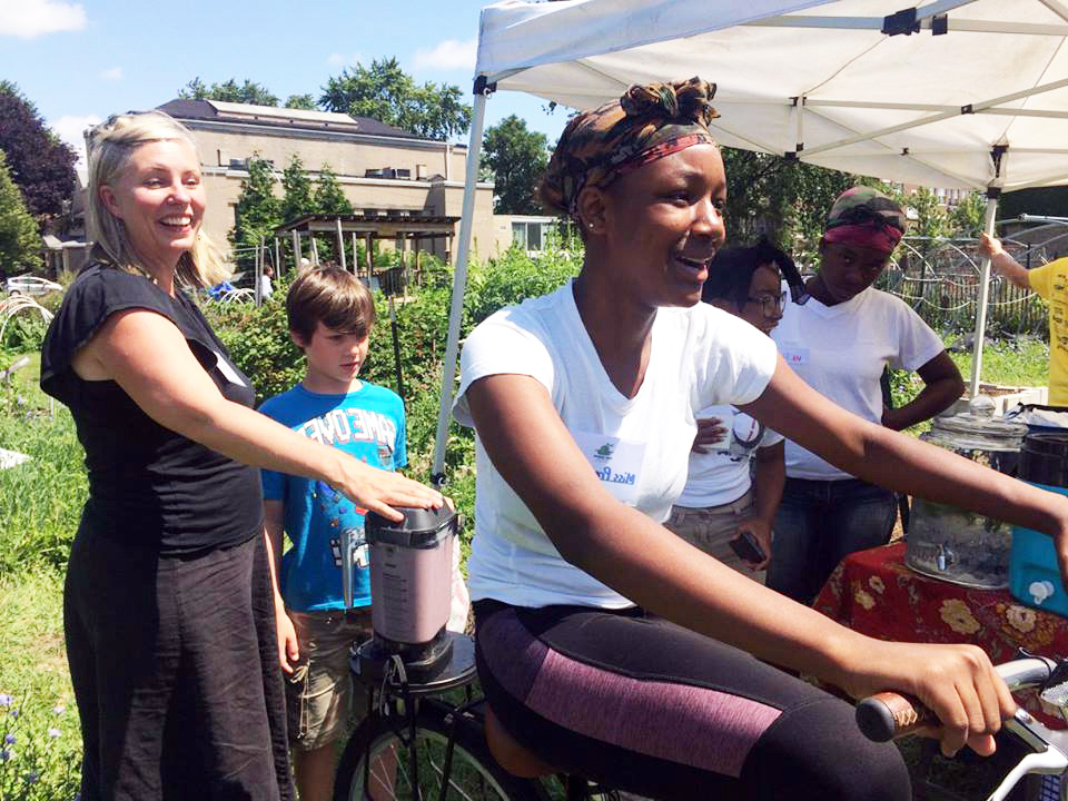 I Can Fly youth use energy generated by the blender bike to make smoothies with Cheryl Munoz of Sugar Beet Schoolhouse.