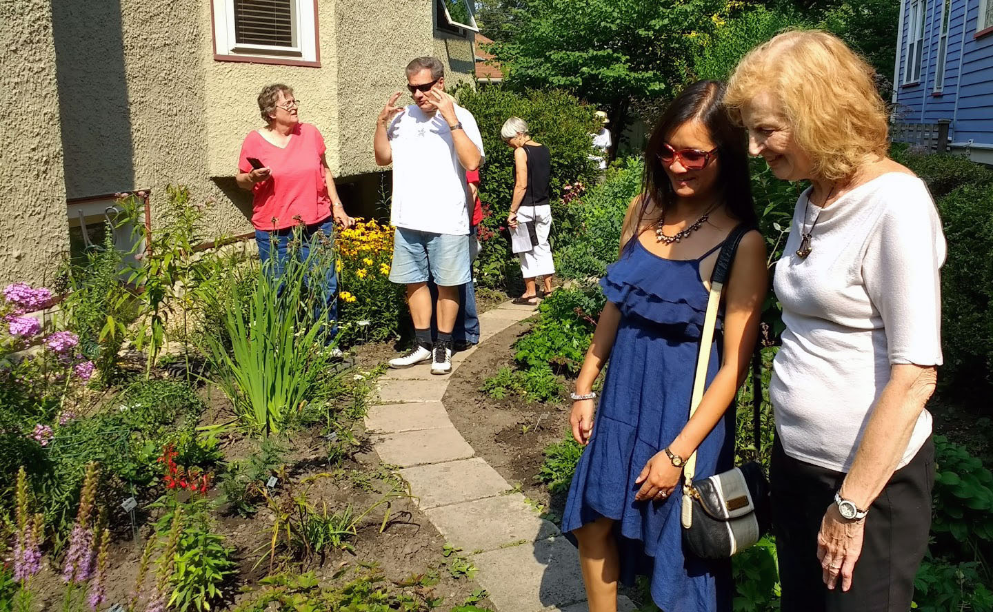 Mary Ann DeBruin (far right) shows her native plants to Michelle Cronin. Mary Ann's garden was one of 15 private and public native gardens on tour during peak season.