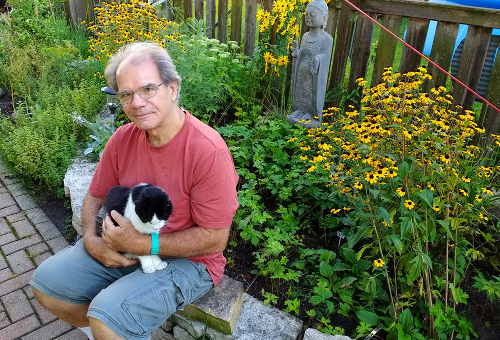Jim Gill and his alley cat, Itchy, take a break near native blue mountain mint and brown-eyed Susan.