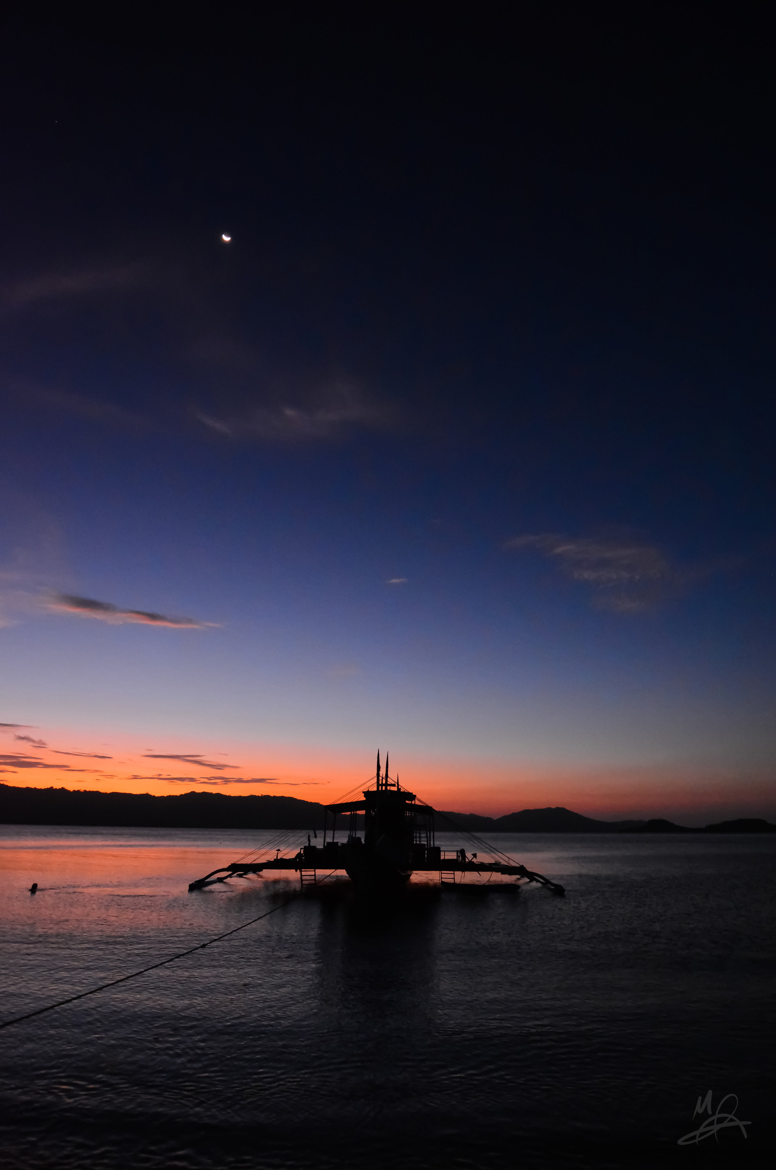 Vessel accompanied by the moon at sunset