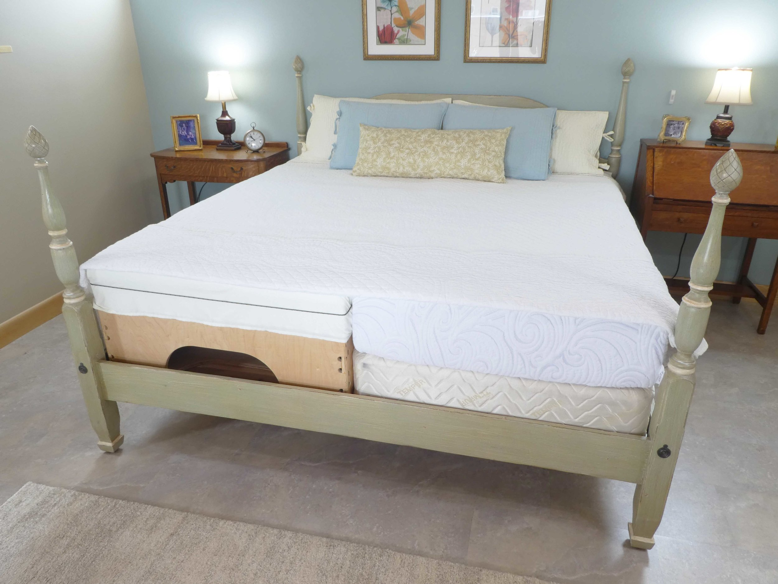 The end of the bedspread has been pulled up to reveal the microtraction bed,  box platform, and mattress underneath.