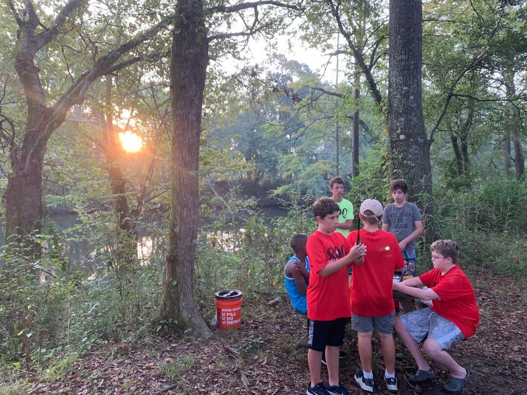 - sunrise over the Lower Mountain Fork River with Scouts preparing breakfast