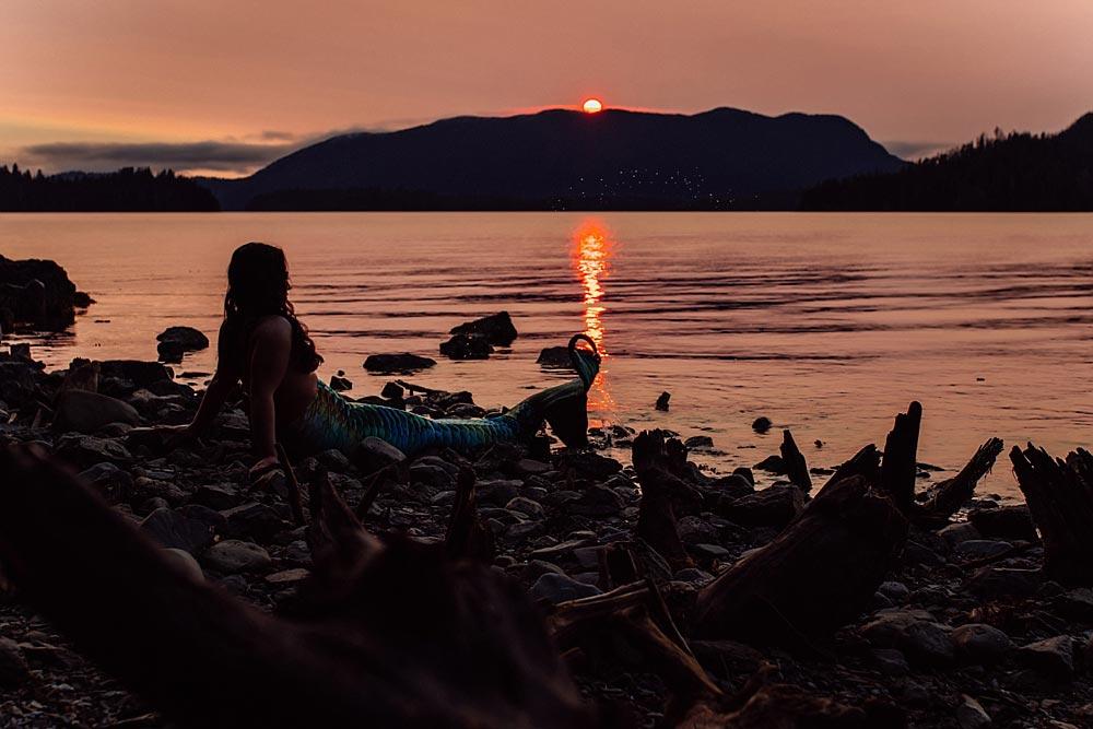 mermaid-sits-on-rocky-coast-in-juneau-as-sun-sets.jpg