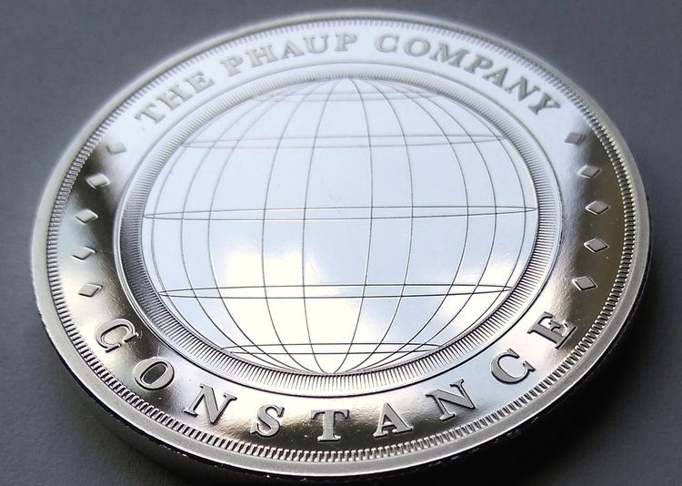 Obverse side: The prize given quarterly, a one ounce .999 fine silver 'Constance' round by The Phaup Company, llc.