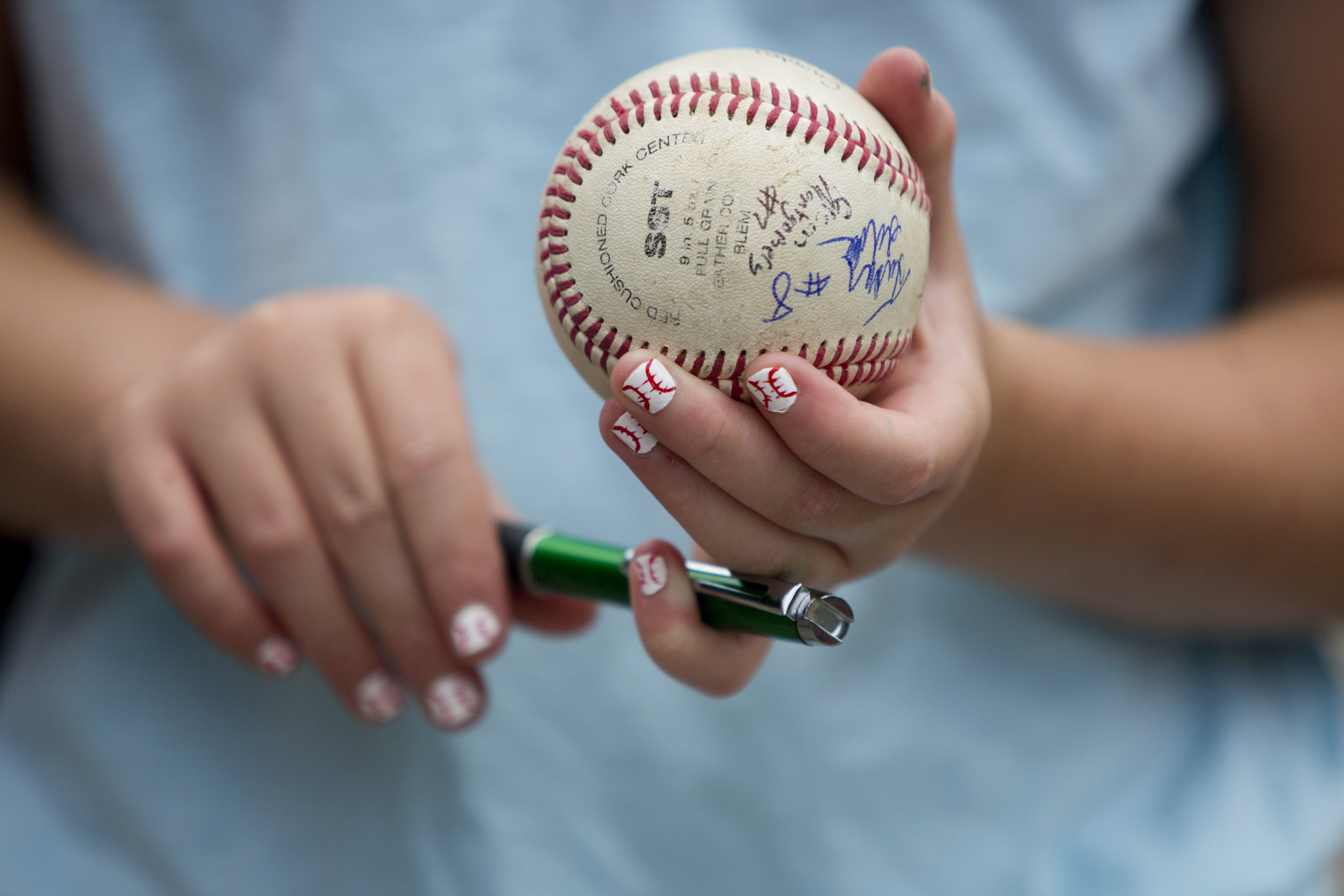 Ellie Bardwell of Huntingburg, 11, got her nails painted like baseballs at a salon before the Southridge High School send-off to the state final game at League Stadium in Huntingburg, Ind. on Friday, June 15, 2018. Bardwell, the daughter of athletic director Brett Bardwell, collected Raider signatures on her baseball.