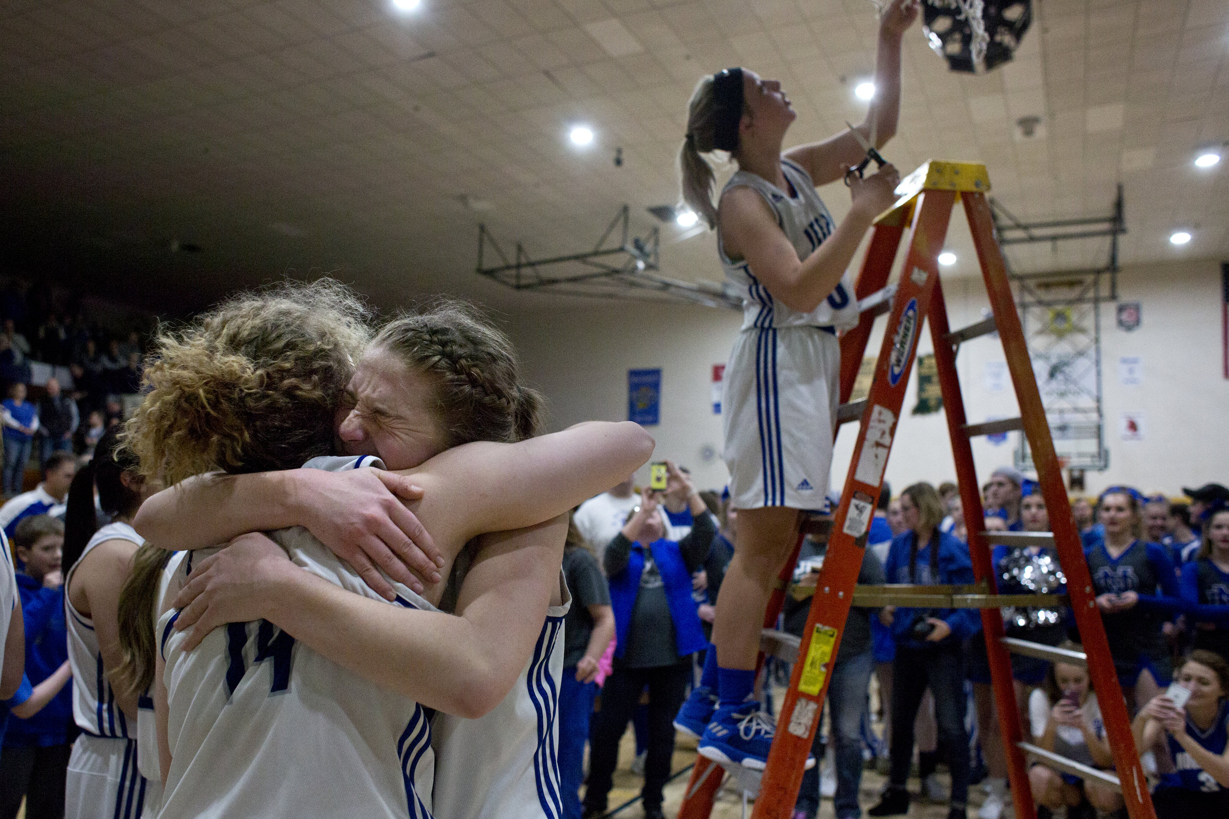 Northeast Dubois' Clare Mangin and Tyla Rasche embraced while Kortney Quinn cut the hoop down after defeating Wood Memorial at Wood Memorial High School in Oakland City on February 3, 2018. The Jeeps won 35-30 to claim the Class 1A Sectional title.