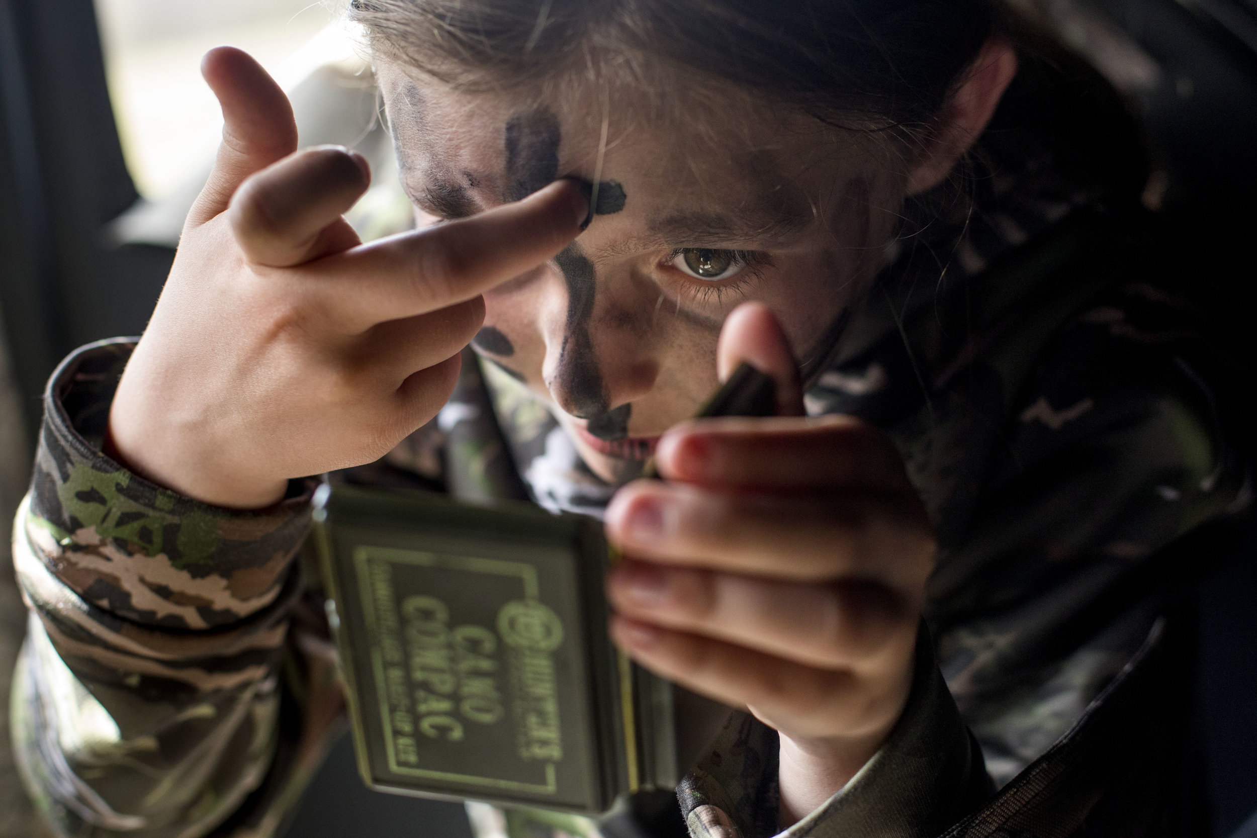 """Maris Drew of Jasper, 11, applied camo face paint in the hunting blind at the Youth Turkey Hunt at Patoka Lake, Ind. on April 21, 2018. Drew's hunting guide Shannon Gillette of Markleville brought the camo face paint, and said that the face paint is """"sacred"""" to her."""