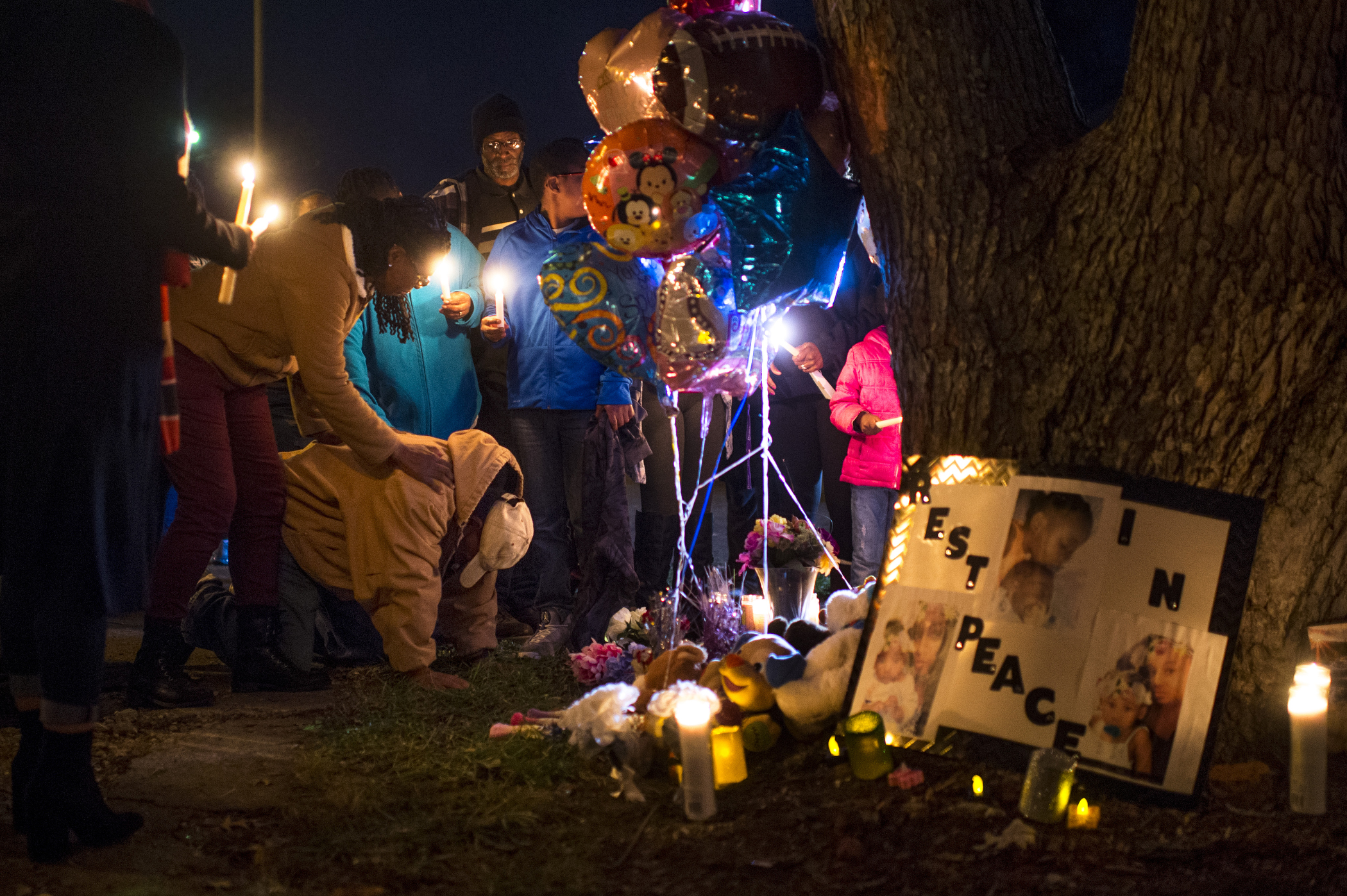 "Dwayne Johnson, father of Janae Carter, kneels after speaking during a candlelight vigil at the corner of Linwood and Monroe avenues in Evansville, Ind., on Thursday, Nov. 30, 2017. Johnson is the grandfather of Prince Carter, 7 months, and Princess Carter, 2, who both died as a result of the crash at the scene following a police chase the evening of Wednesday, Nov. 29. ""They took my babies away from me,"" said Johnson, before he knelt to the ground."