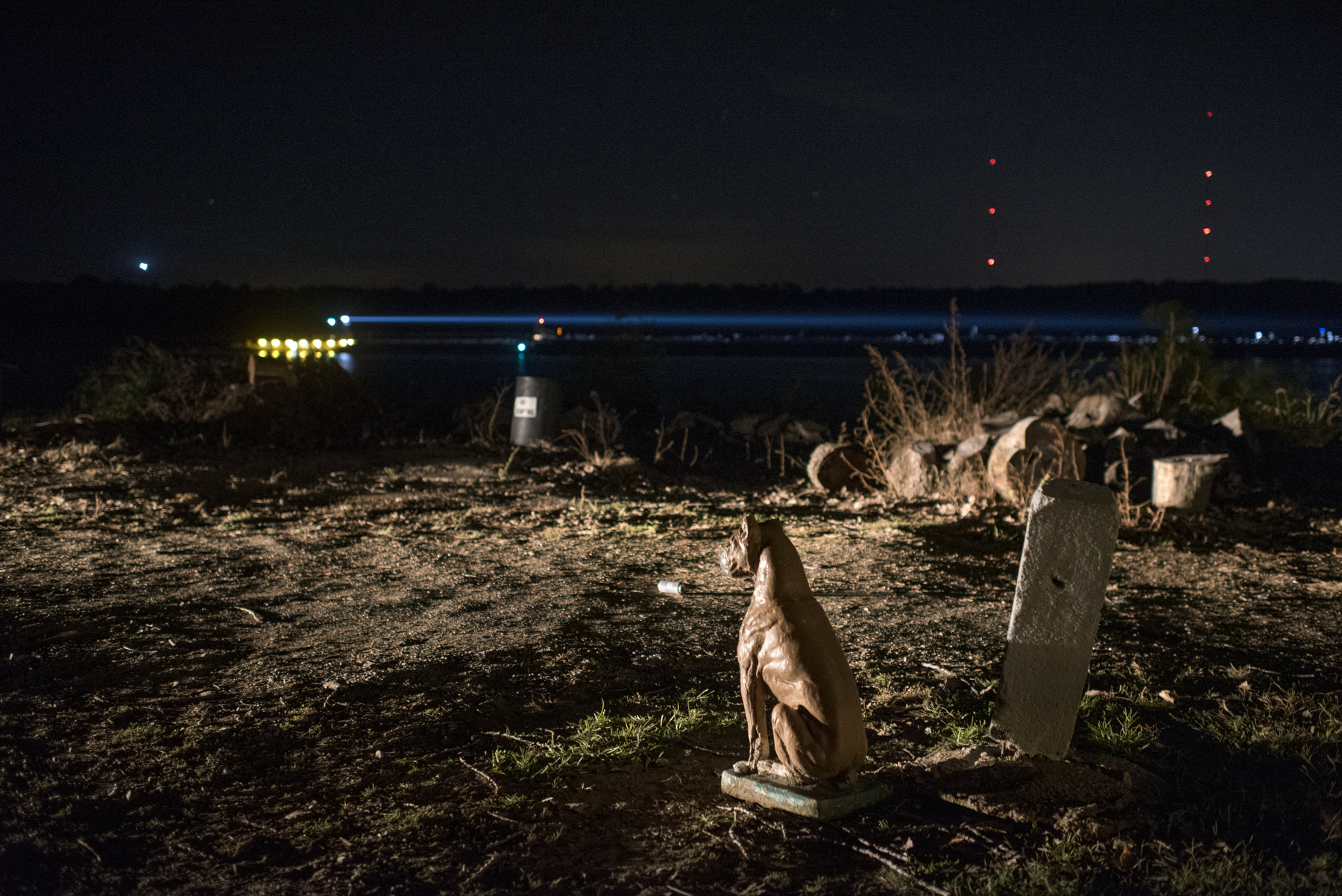 Decorations are a part of the riverbank culture. A plastic dog guards the dirt road along the camps while a barge passes in the dark in Dade, Ky. on Oct. 22, 2017.