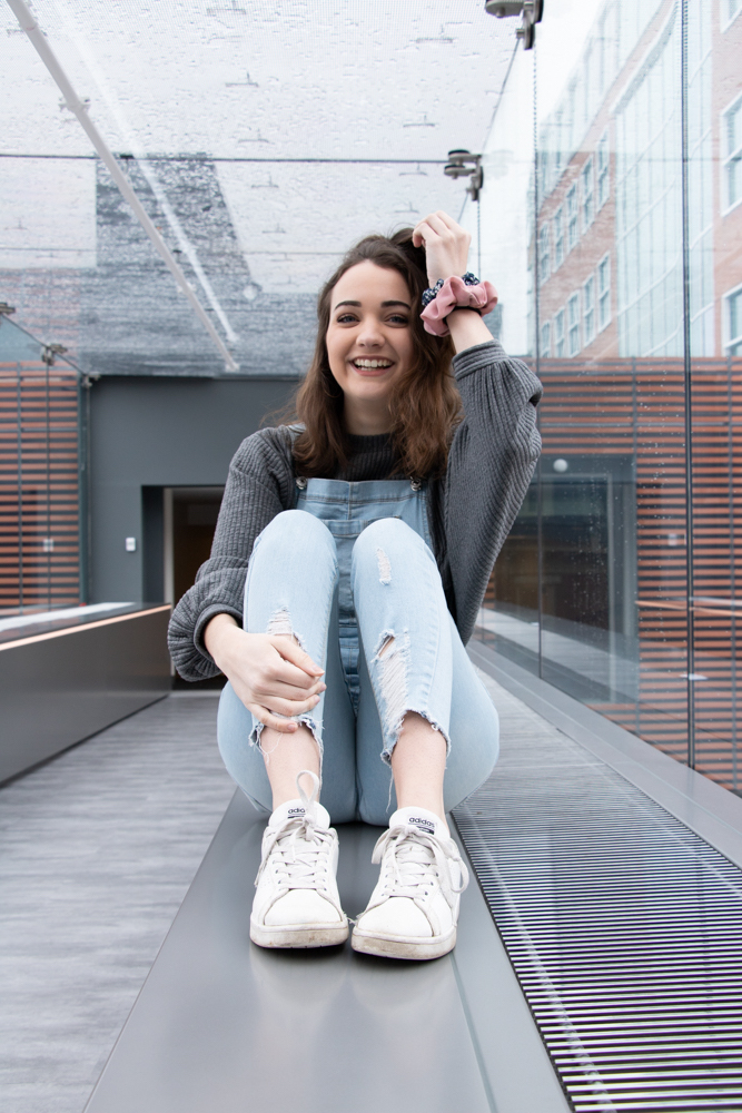 Magdalena Becker, a junior journalism major, sits in the Skywalk connecting Alter Hall and 1810 Liacouras Walk. | HANNAH PITTEL / REFINE MAGAZINE