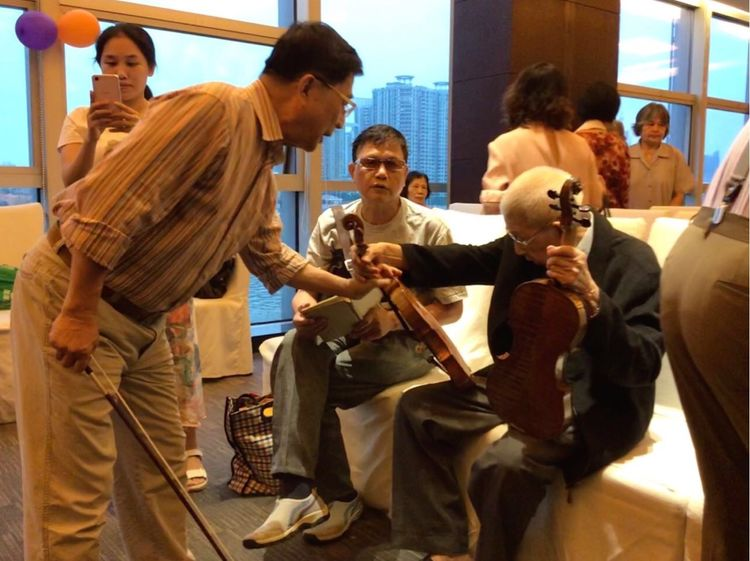 Master Chinese Violinmaker Liang Guohui inspects violins on the occasion of his 95th birthday.