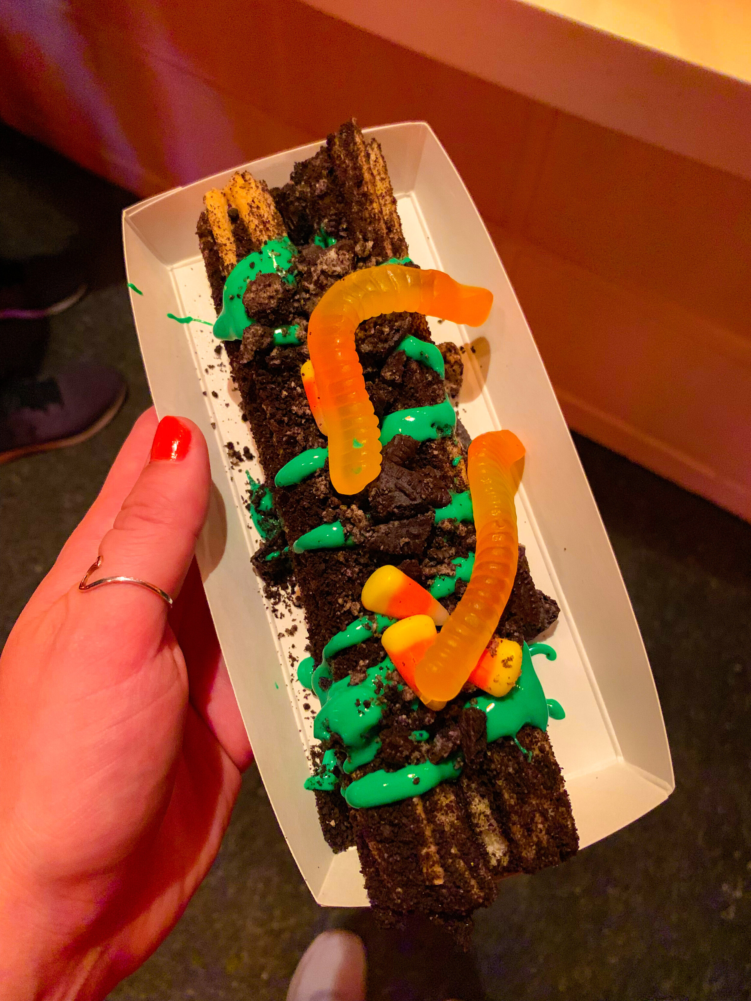 Haul-O-Ween Churro,  a churro rolled in Oreos, green icing, gummy worms, and candies
