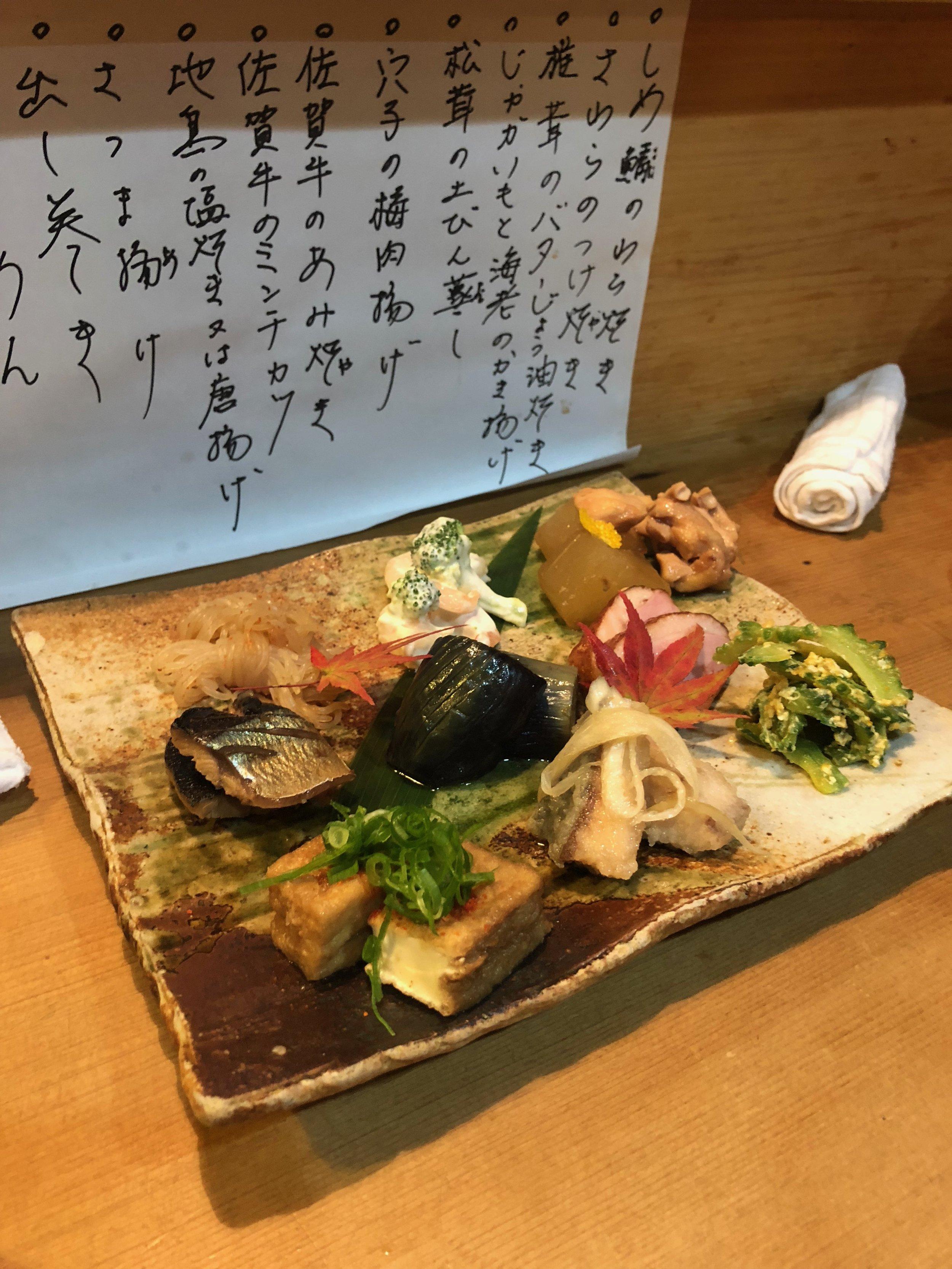 Un plato de comida con diferentes tipos de pescado, carne, vegetales, y fideos. Y hojitas de otoño como adorno.