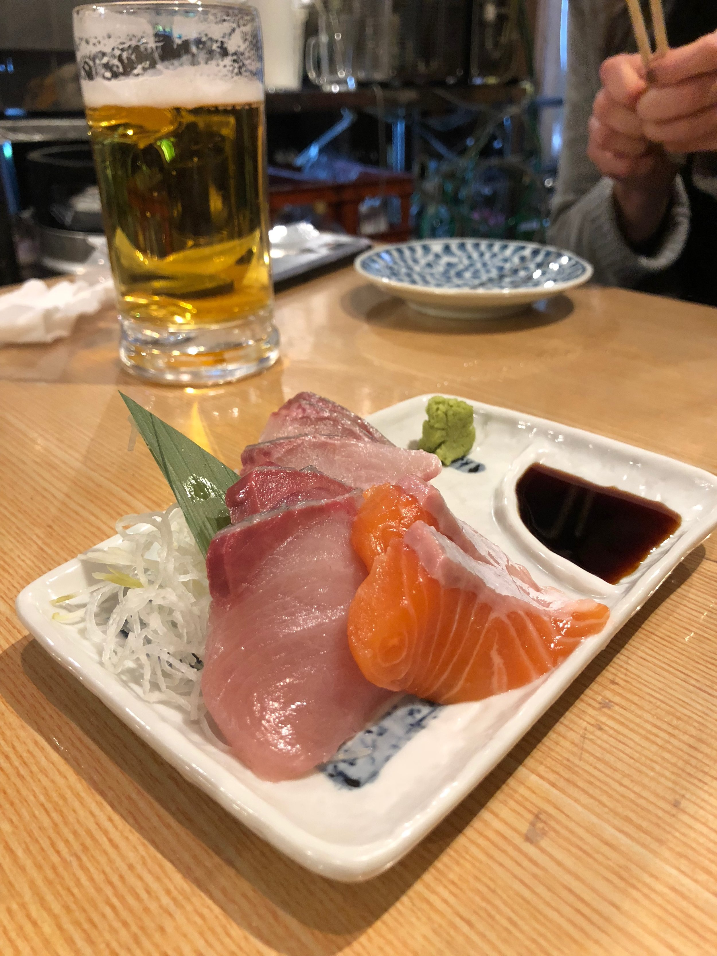 Pescado de salmón y atún cortados con wasabi y salsa soya a lado.