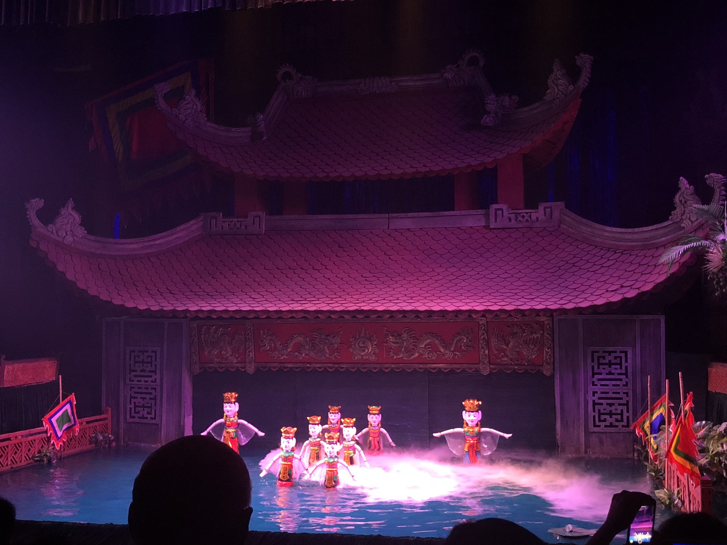 A scene from the Thang Long Water Puppet Theatre. There is a small orchestra and two singers who describe a story of the Vietnamese countryside and the puppet masters are behind the temple gate.
