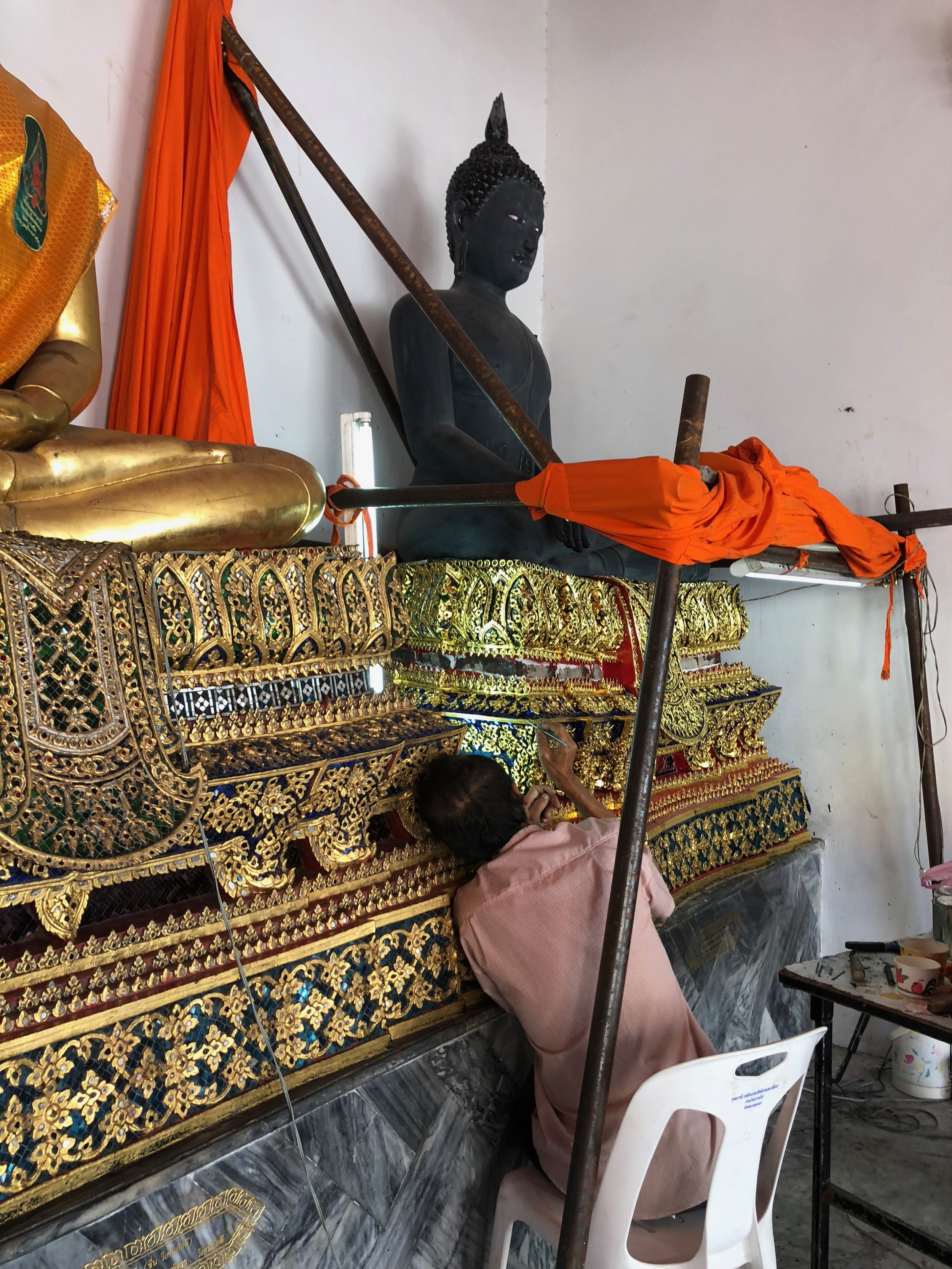 A photo I caught of someone working on the decoration of a statue in Wat Pho. I think he was adding jewels into the embellishments.