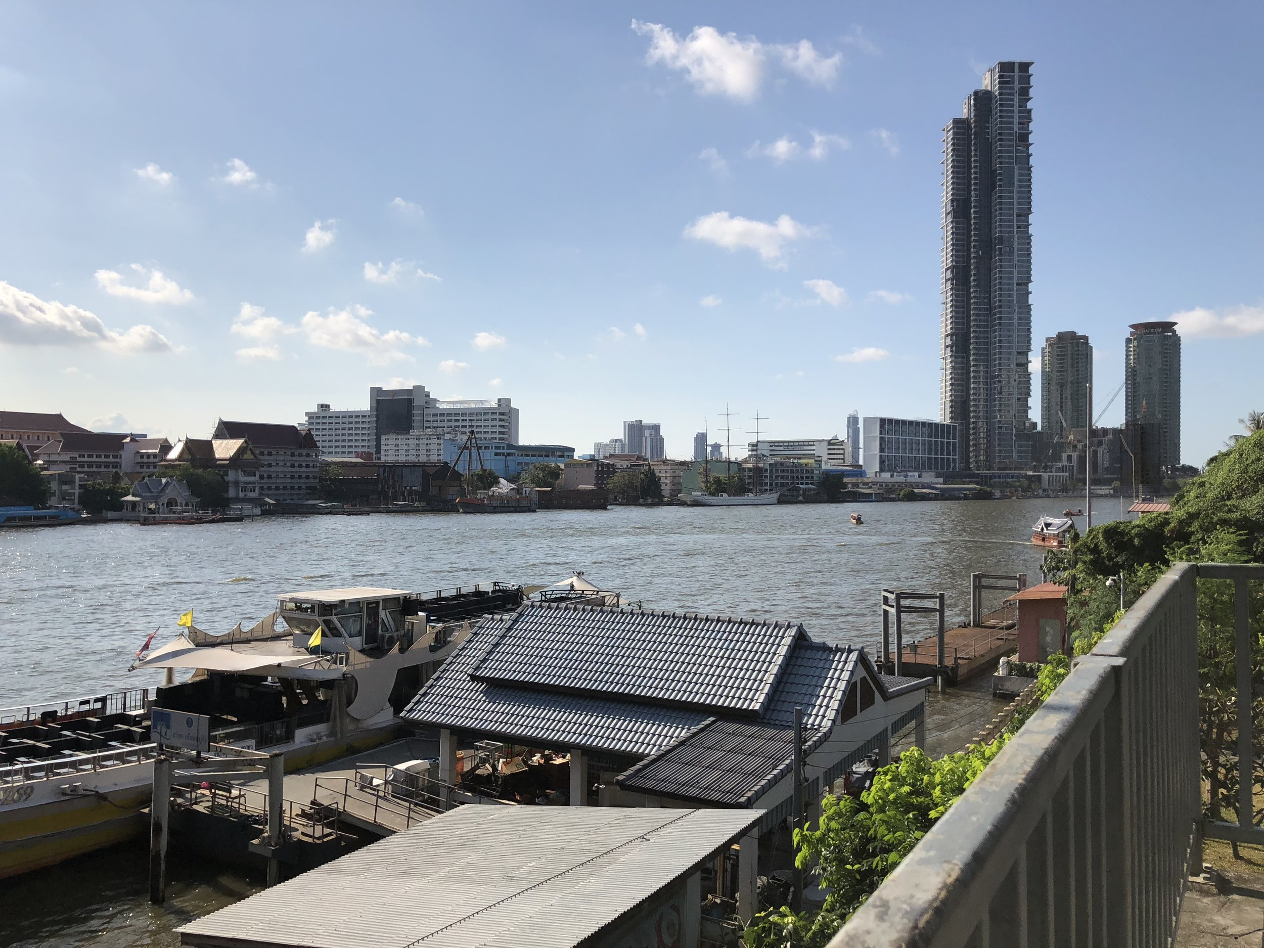 La vista de Chao Praya y un muelle con barcos para transportar la gente desde un puente.