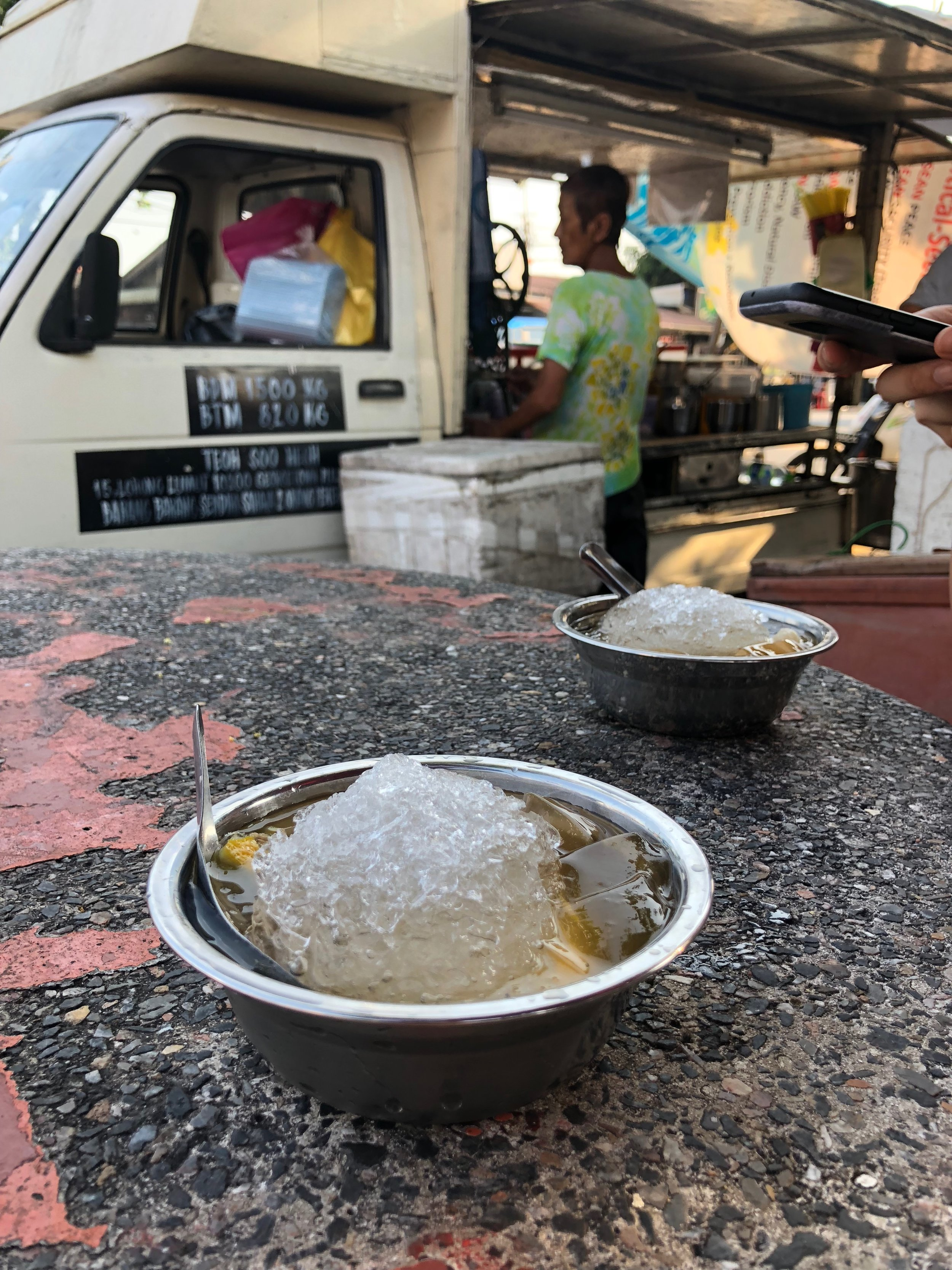 Orh kioh - shaved ice with jelly, a slice of lime, and longan, a lychee-like fruit—a refreshing treat from Penang. Behind you can see the food cart selling this icy treat.