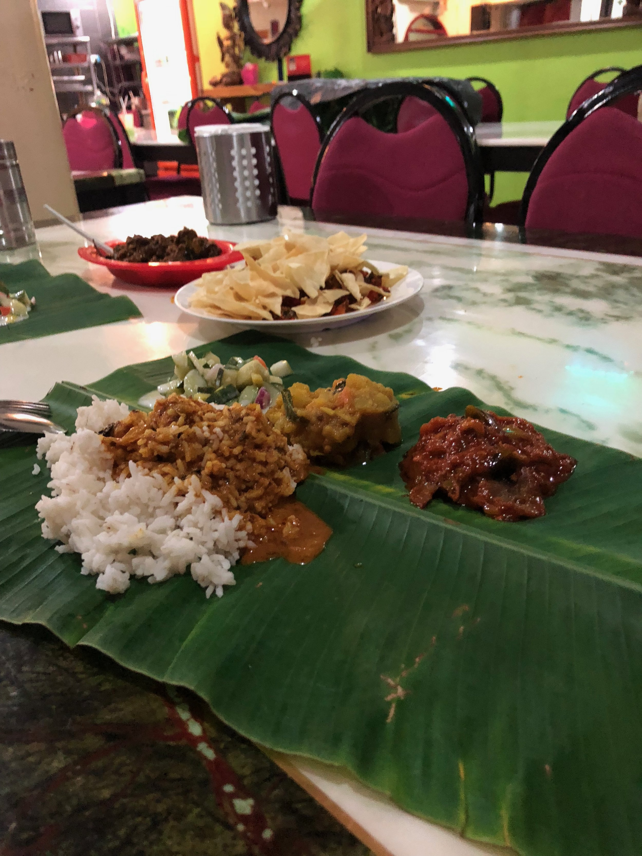 "Another Malaysian-Indian staple: banana leaf restaurants! In red bowl in the back of the photo is dry lamb curry. On top of banana leaf ""plate"" is an assortment of vegetarian side dishes (vegetables in yogurt, dhal, and chutney) and white rice covered in the least spicy curry they had to offer…because my tolerance was so low!"