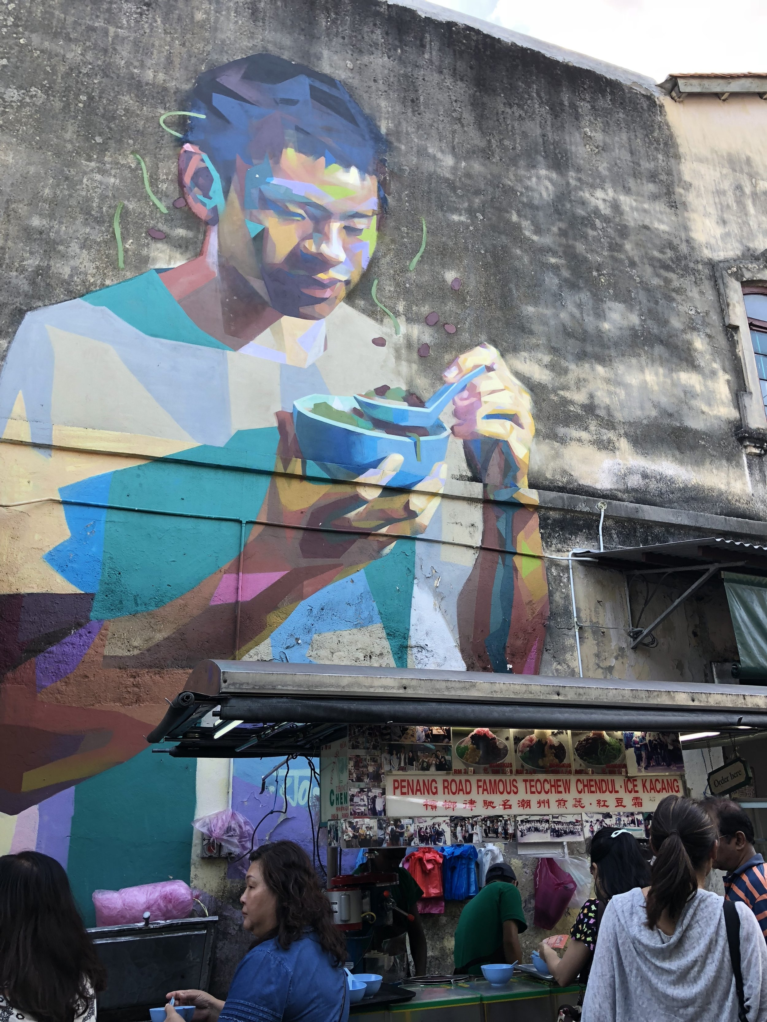 Above the street cart selling chendul, a noodle and tea beverage, is this beautiful mural. A great treat—both the chendul and the mural!