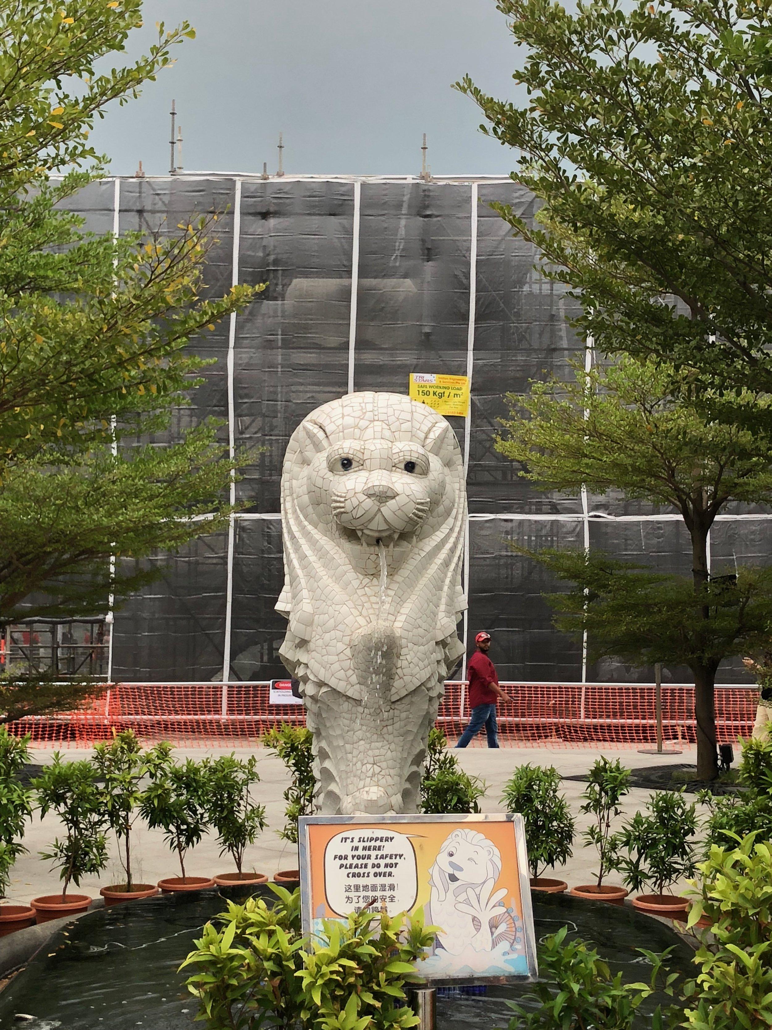 ¡Al final, el Merlion! Esta estatua es un Merlion, parte león y parte pescado. Esta estatua es una versión más pequeña del Merlion real, lo que esta debajo construcción atrás del pequeño Merlion. Camina tanto solo para ver esta estatua pequeñita.
