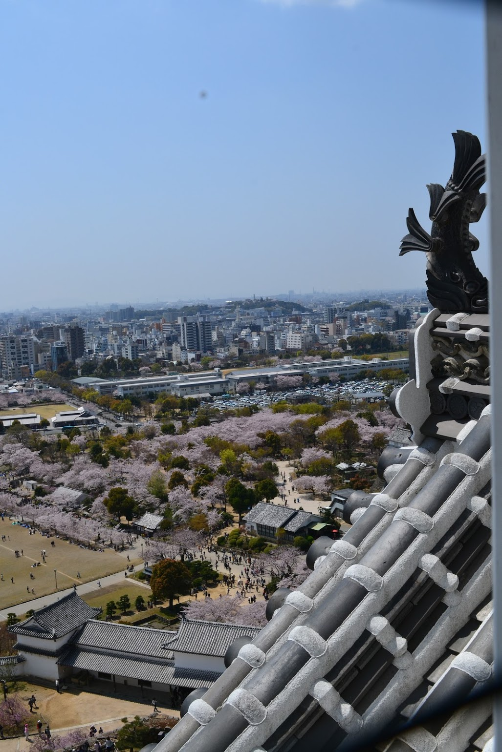 """The view of the castle grounds and the city of Himeji. The roof's """"gargoyles"""" are actually white herons, which is also the nickname of Himeji Castle: White Heron Castle."""