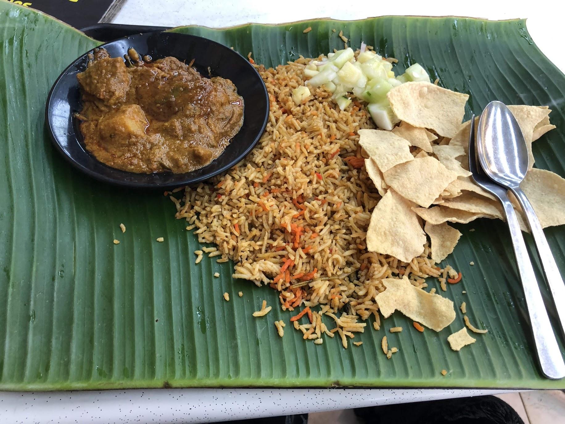 Un plato de comida india: cordero picante con arroz frito.