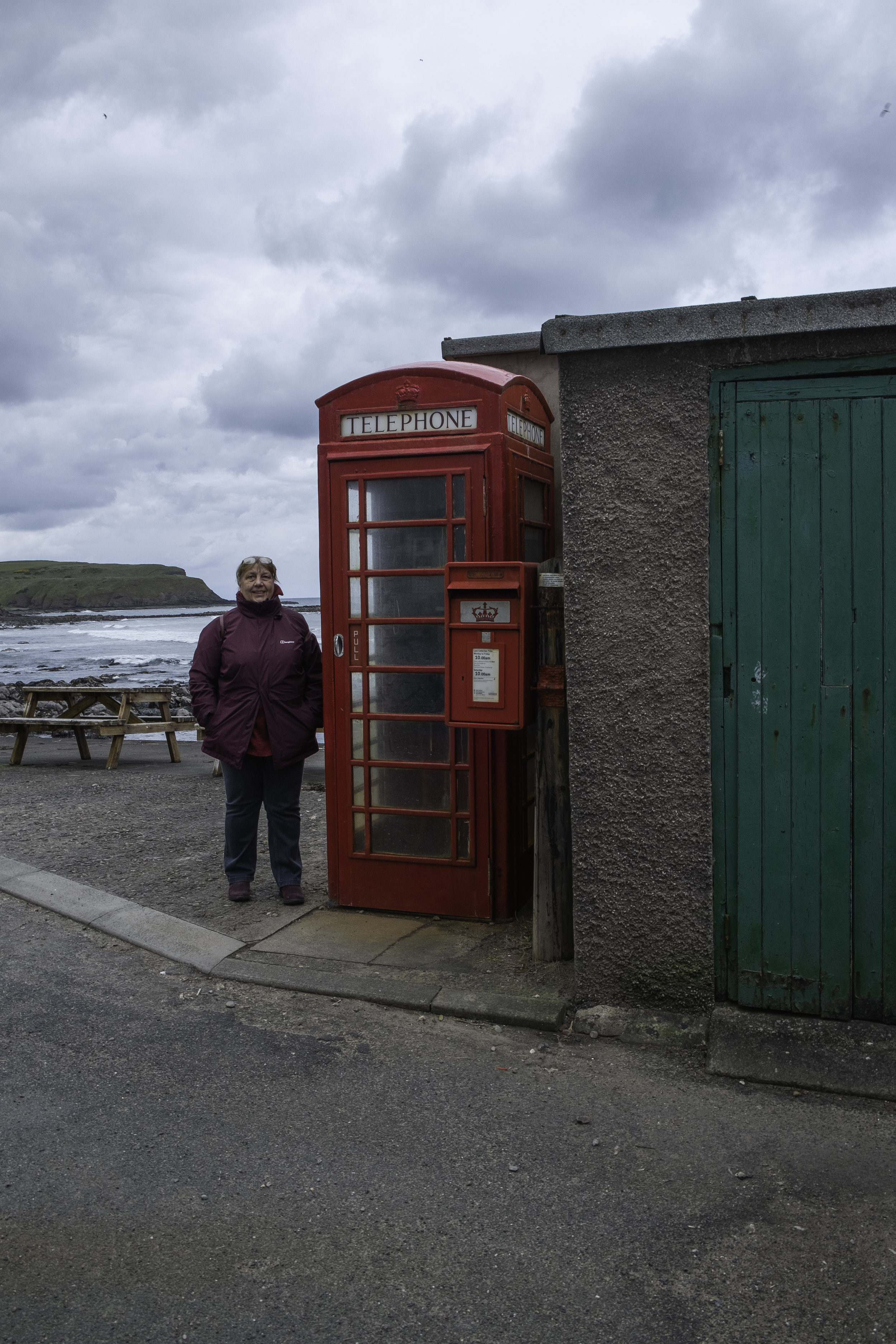 Me by the phone box in Pennan placed there by the Local Hero film makers who used this pretty village as their main village. Just a bit windy and cold that day