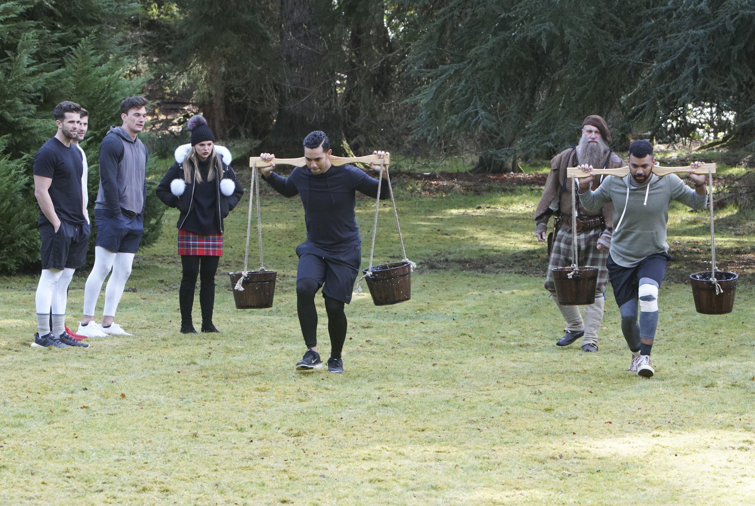 Kendrick (right) carrying weighted buckets with fellow contestant Devin Harris on a group date in Scotland
