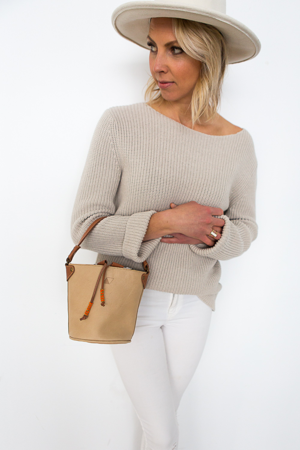 White jeans and a beige sweater paired with our    Mini Keri Bucket Bag   ,    Eliza Ring   , and a cream hat.