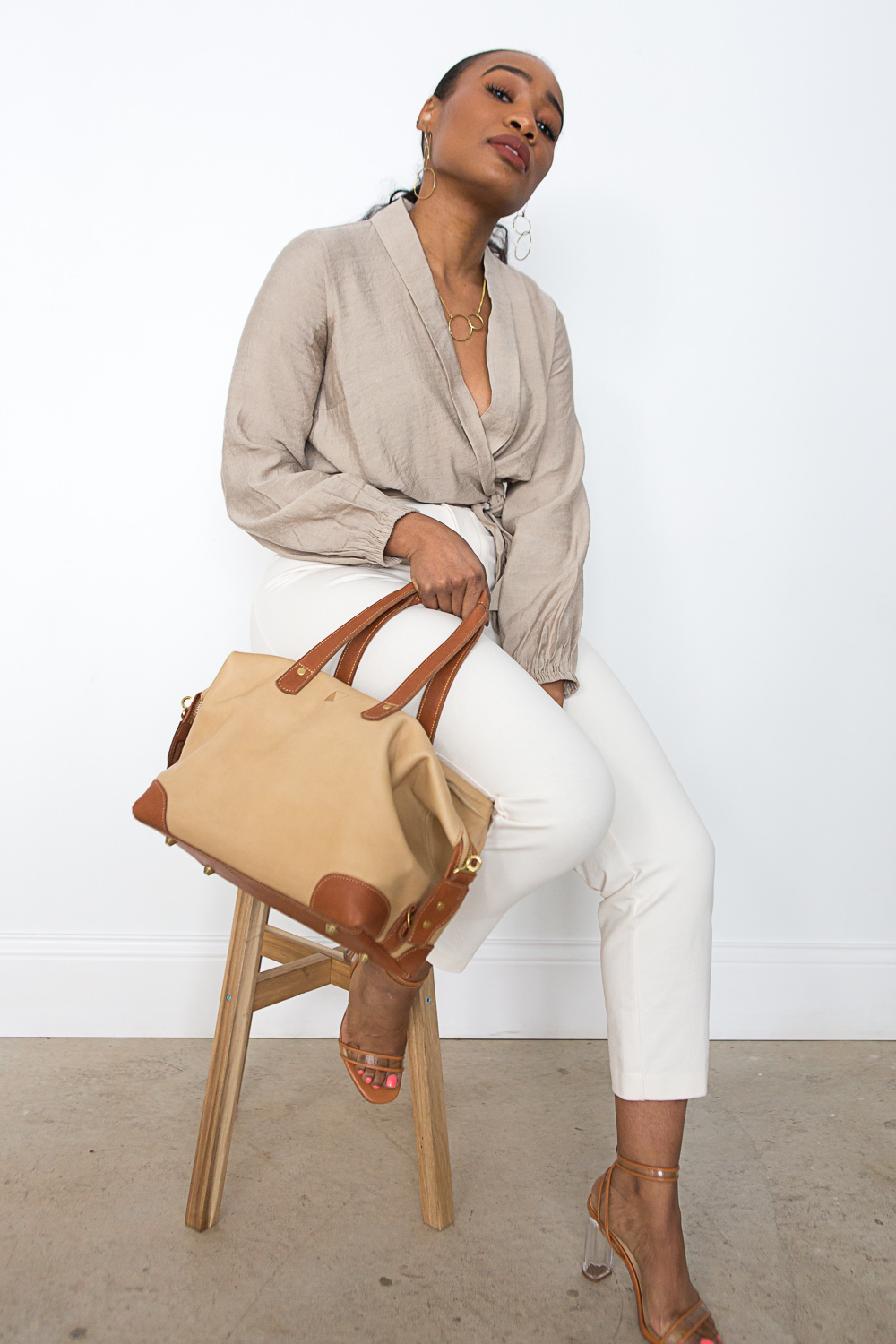 White capris and a beige top paired with our    Ellen Handbag    in sand, our    Heritage Necklace    and    Earrings   , and clear and caramel heels.