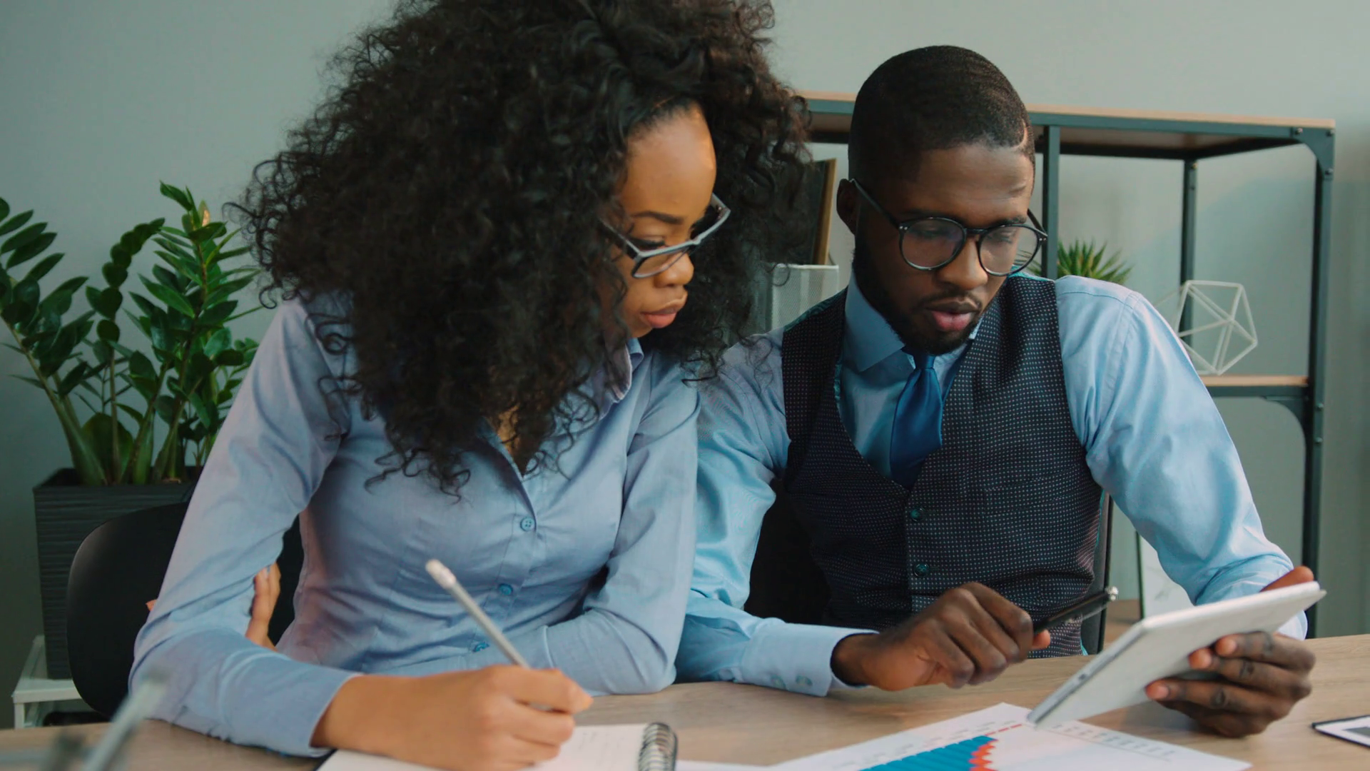 videoblocks-team-of-two-african-american-business-people-working-together-in-the-office-african-american-businessman-and-businesswoman-talking-using-tablet-computer-checking-financial-charts_rh-g8g3eb_thumbnail-full01.png