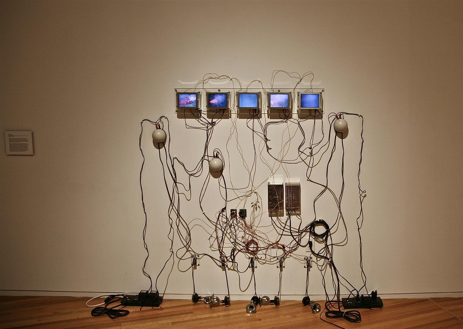 """Flashcracker   LCDs, media players, acrylic, servos, horns, drivers, amps, electronics, sand  36"""" ring of sand / 6-8' of wall space / 2007"""