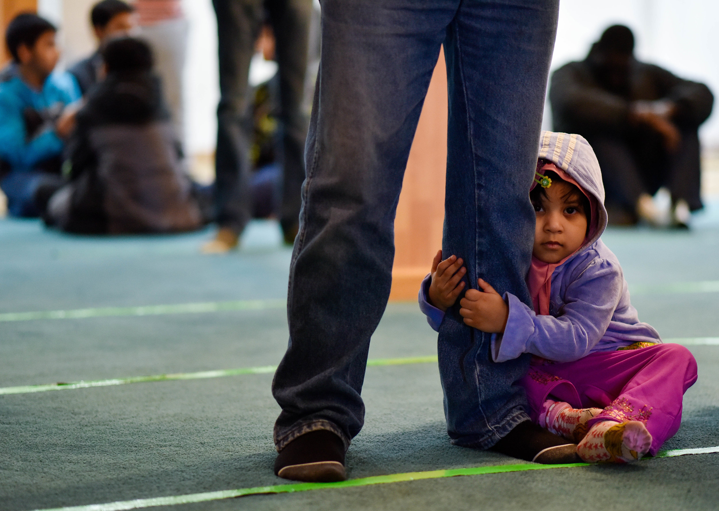 Maliha Uddin, 2, clings to her father Forkan's leg before Friday afternoon service at Masjid Al-Noor.  Forkan immigrated to the US from Bangladesh 30 years ago.