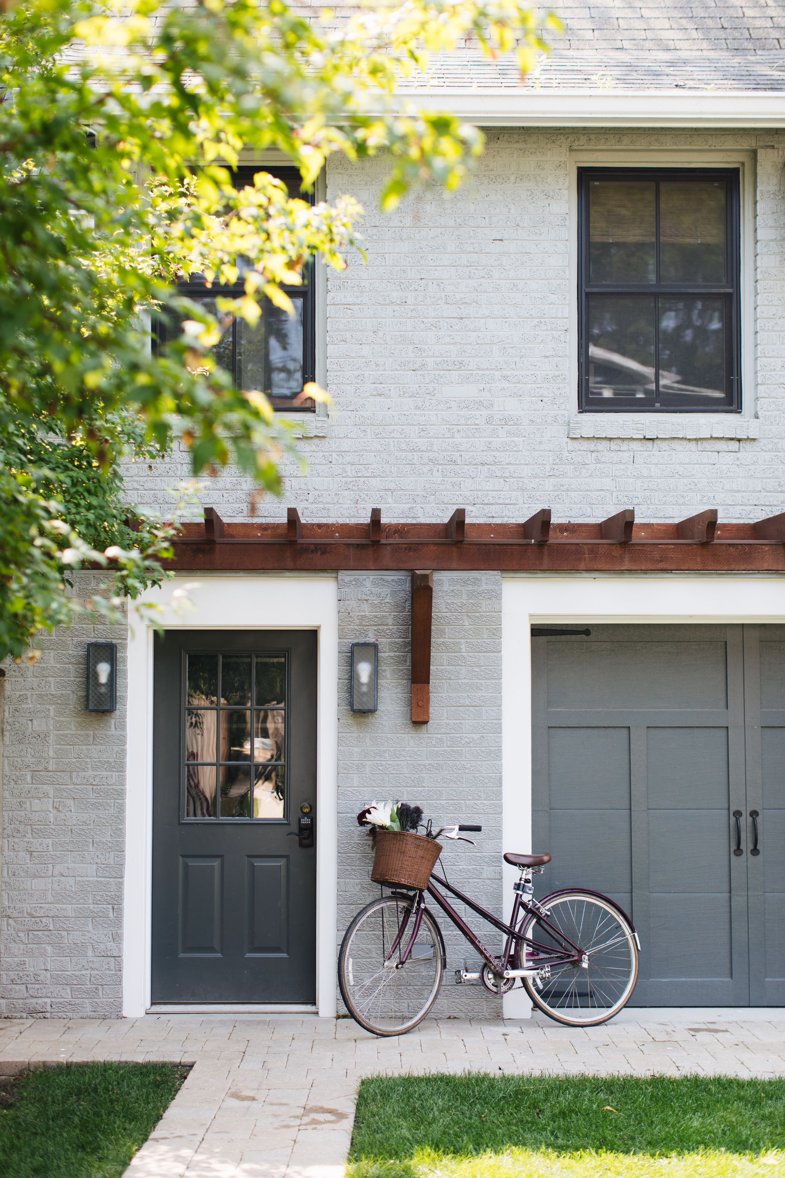 Hogan Kelly Design Coach House with Gray Painted Brick and Black Windows and Dark Wood Timber Trellis and Party Garage Door.jpg