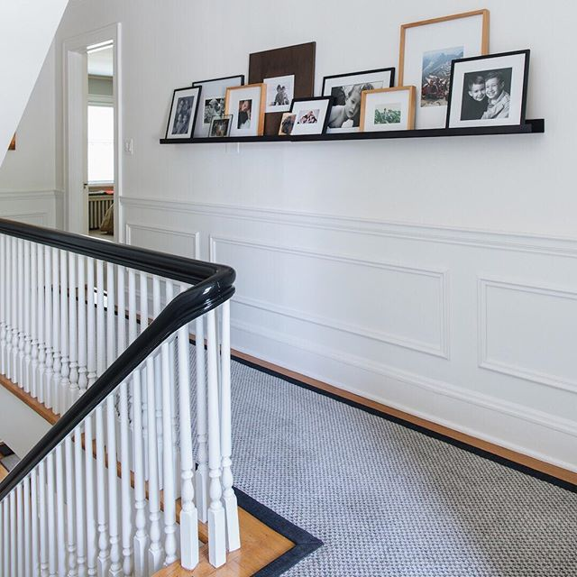 "We love making homes with ""good bones"" even better. Believe it or not, this pretty Georgian-style home didn't always have this wainscoting, nor a high-gloss black railing. Now with the white millwork and walls coupled with the painted black railing, you can appreciate the graphic elegance of the original staircase. Then this sweet custom runner steps up to tie it all together with perfect shades of gray and it's own dark-trimmed border. 