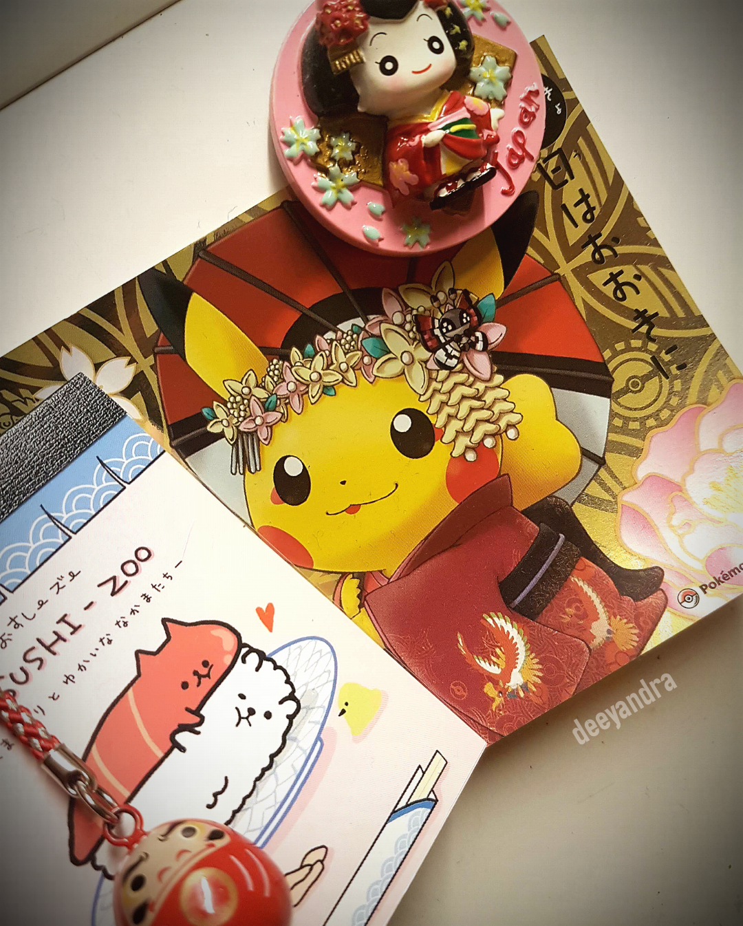 A postcard of Pikachu in traditional dress, a magnet from Kyoto, a mini noteboook with cuddle sushi, and a Daruma keychain for luck